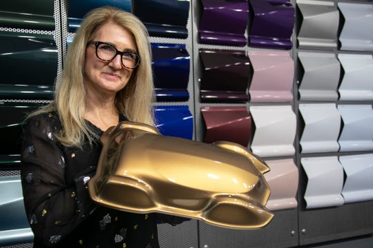Axalta color marketing manager Nancy Lockhart, holds up a sample of the color Sahara which the coating company says will be the most popular vehicle color of 2019.