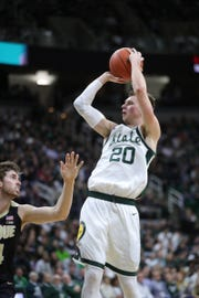 Michigan State guard Matt McQuaid scores against Purdue guard Ryan Cline during first half action Tuesday, Jan. 8, 2019 at the Breslin Center in East Lansing, Mich.