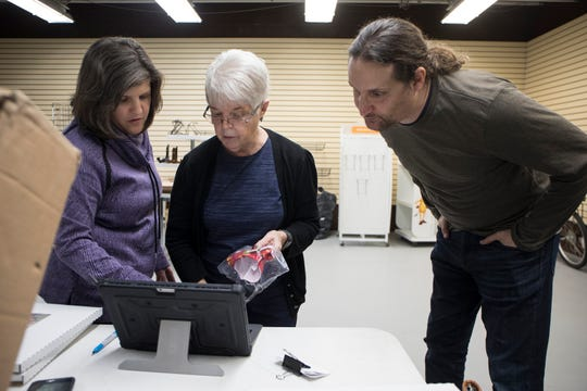 From left, Toni Cooper, executive director of the River Raisin National Battlefield Park Foundation, Carol Burns, gift shop manager and Adam Ginsburg, donor relations work on inventory while the park is closed during the government shutdown in Monroe, Mich., Tuesday, Jan. 8, 2019.