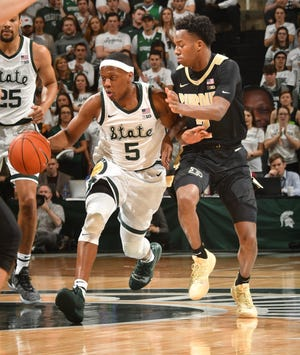 Michigan State's Cassius Winston moves the ball away from Purdue's Eric Hunter during the first half.
