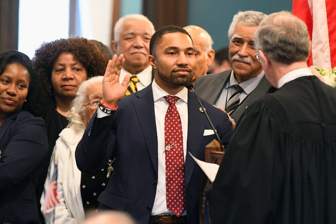 Incoming State Senator Adam Hollier D-Detroit,  is surrounded by his family on the floor of the Senate as he is sworn in by Chief Justice Stephen Markman  in Lansing,  Wednesday, January 9, 2019.