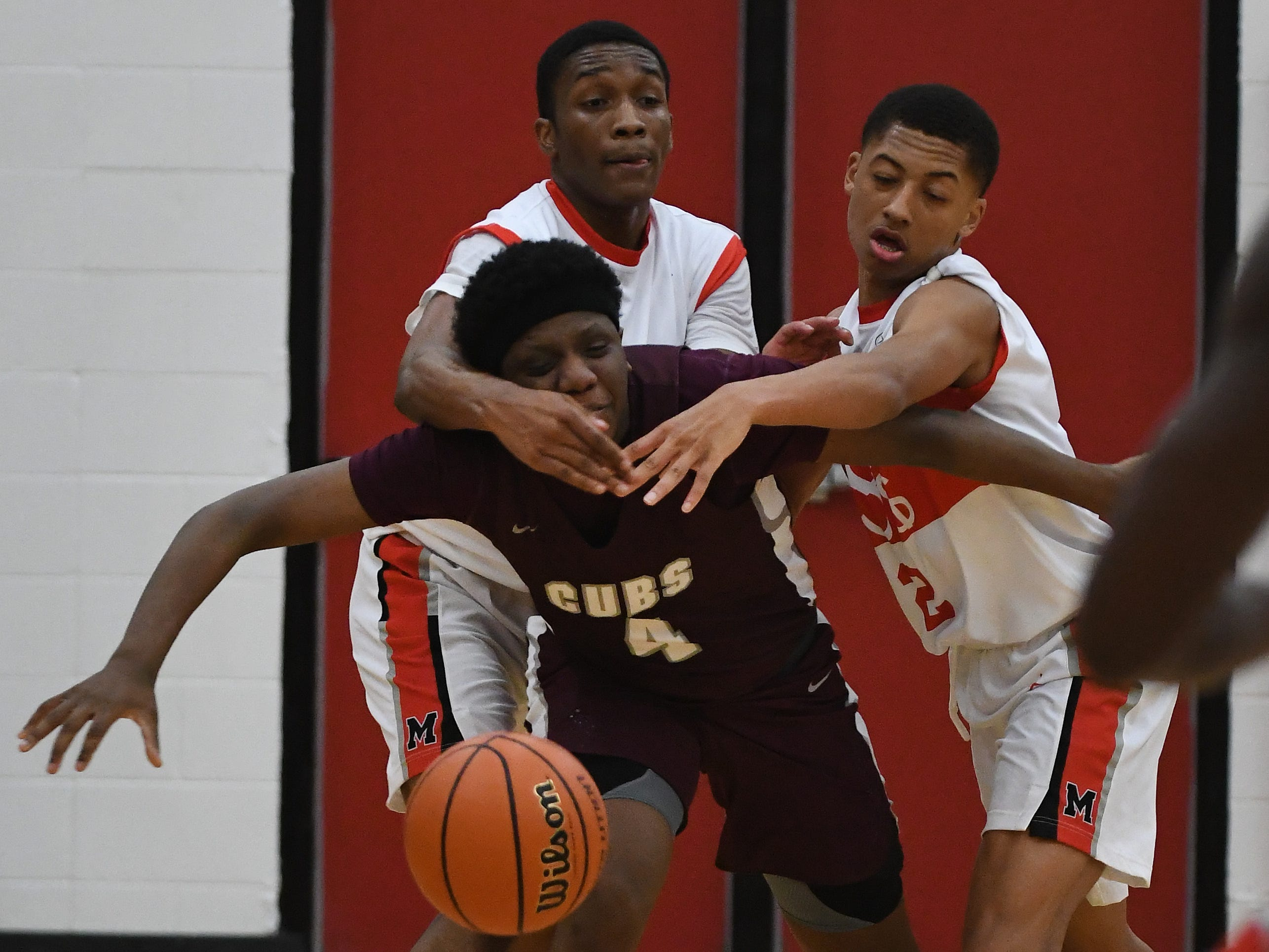 U-D Jesuit's Josh Kashat gets some physical defensive pressure from  Lorne Bowman II and Jason Drake II of Orchard Lake St. Mary's in the second half.