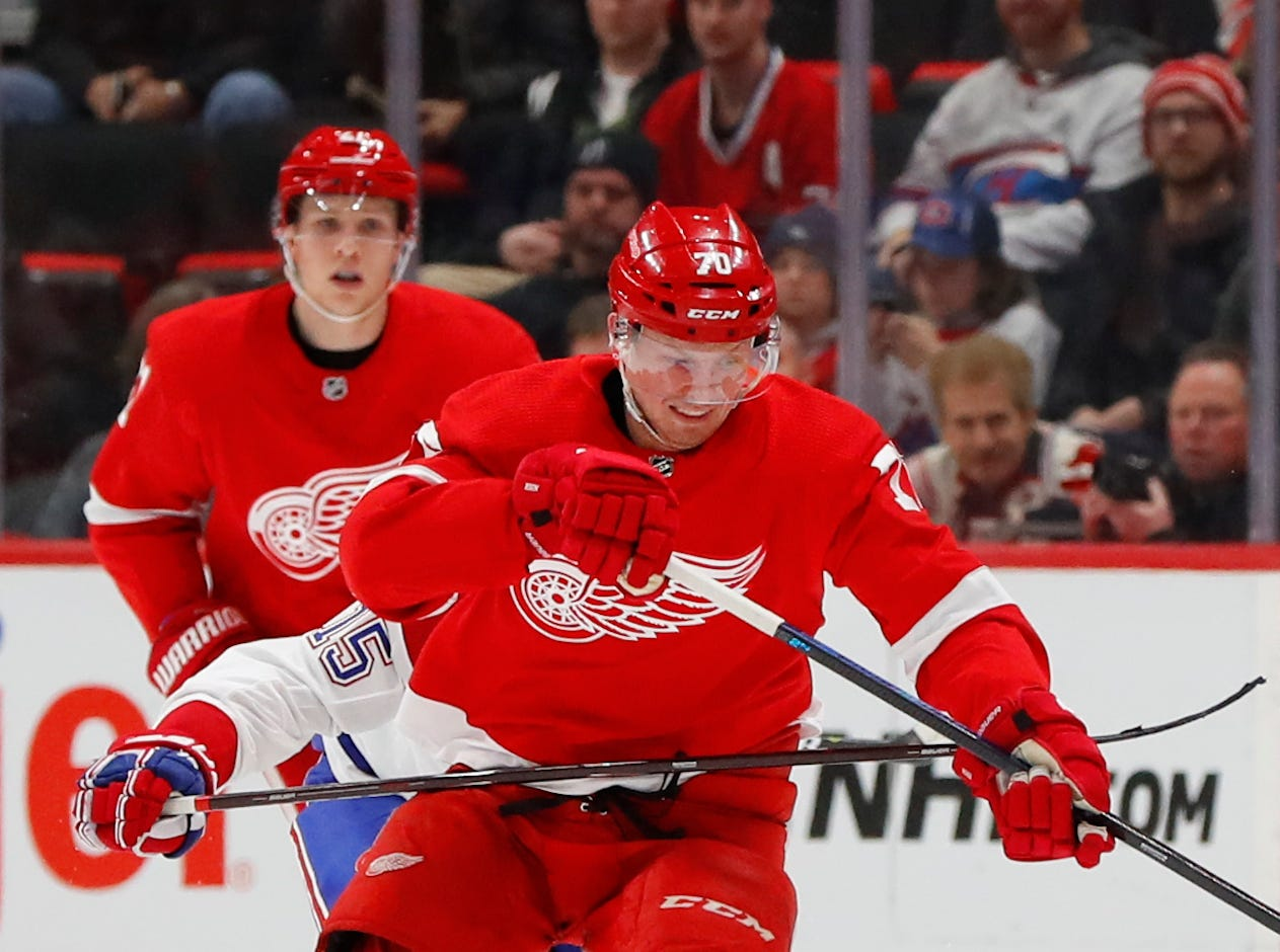 Detroit Red Wings center Christoffer Ehn (70) is hooked by Montreal Canadiens center Jesperi Kotkaniemi (15) in the second period.
