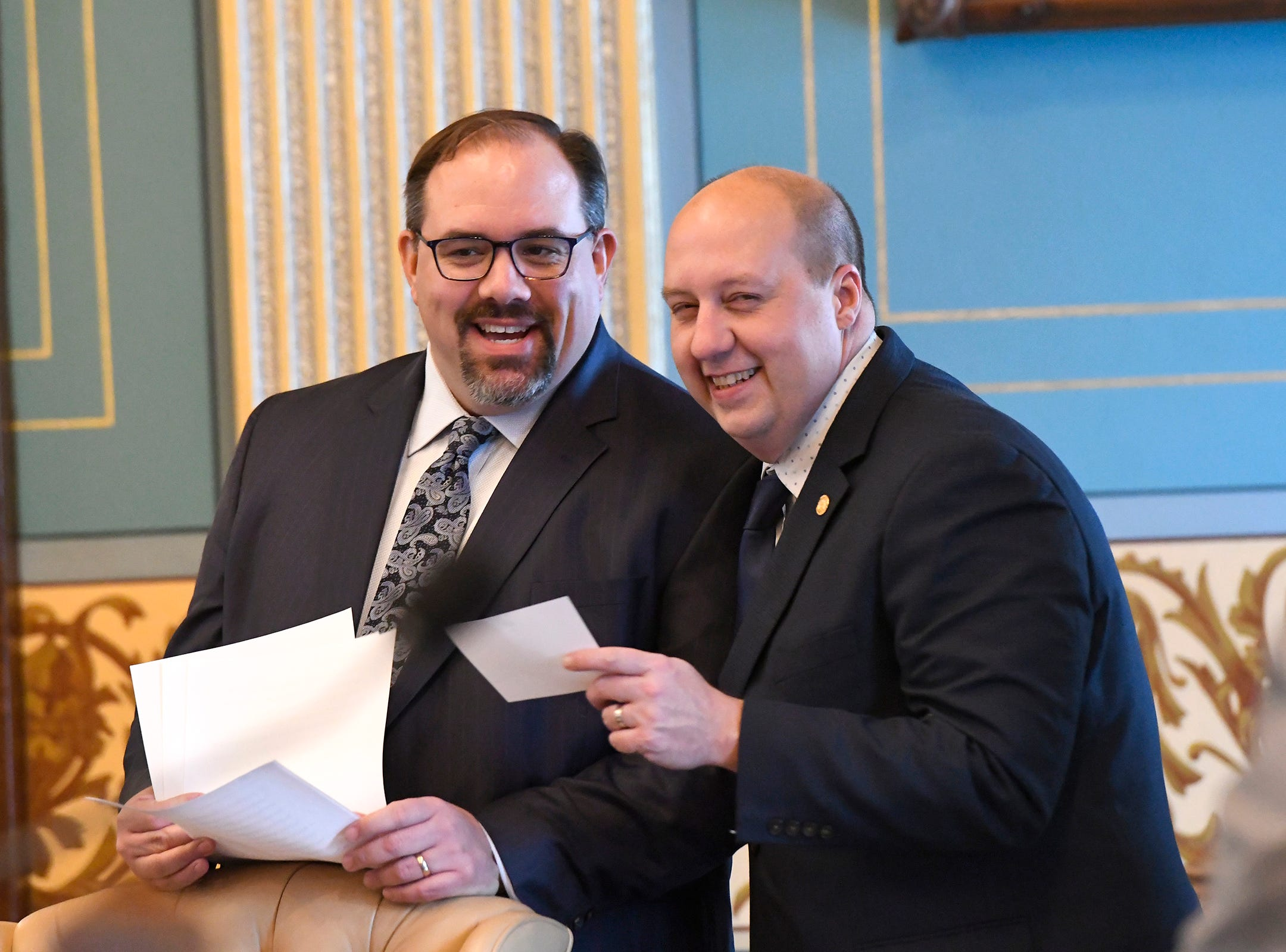 Senate Minority Leader Jim Ananich, left, shares a laugh with Sen. Curtis Hertel, D-District 23, right, before swearing in ceremonies.