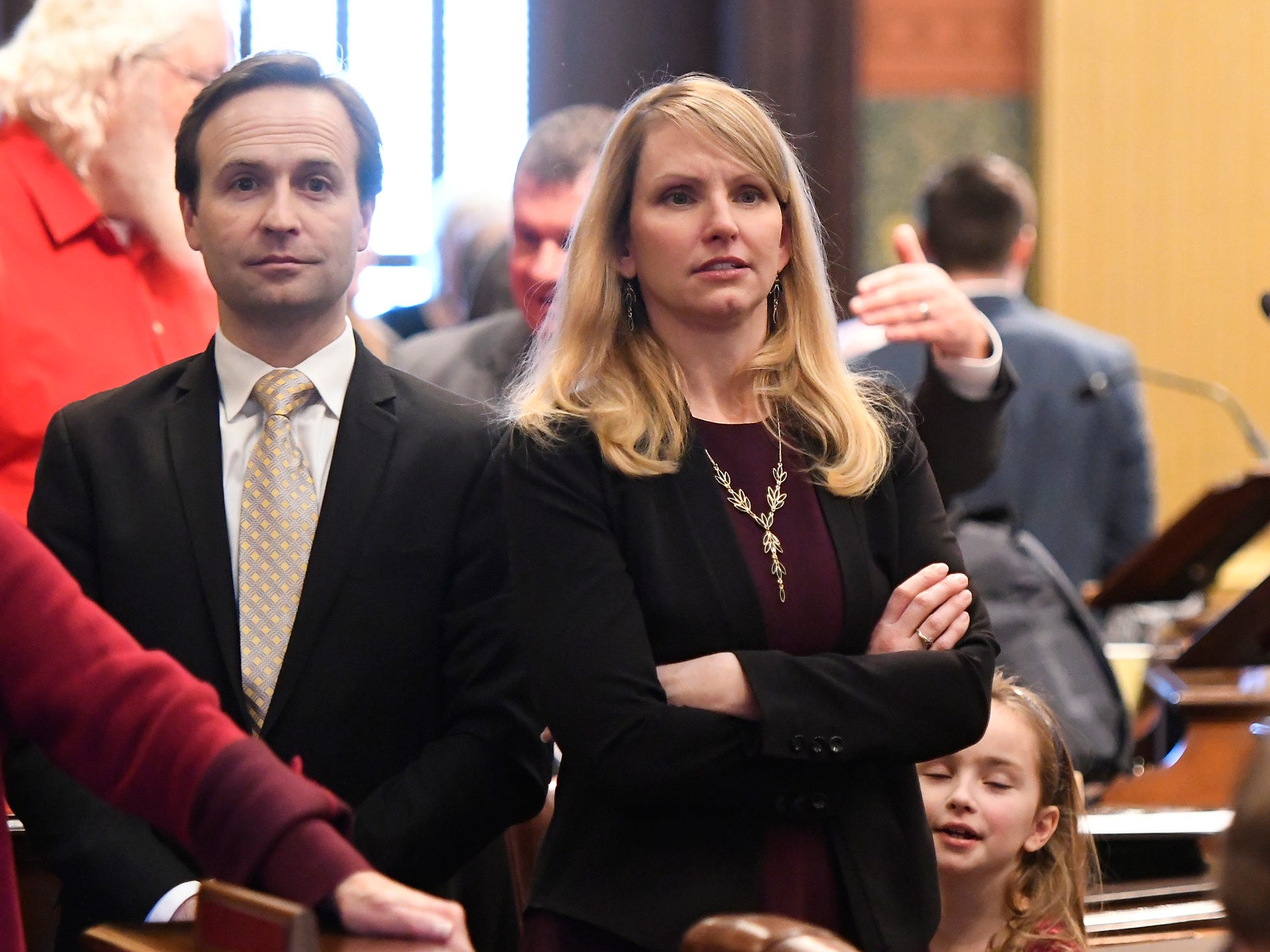 Rep. Julie Calley, R-District 87, and husband (and former Lt. Gov.) Brian Calley, left, wait for Representatives to get to their new seats after swearing in and opening ceremonies for the 100th Legislature Wednesday in Lansing.