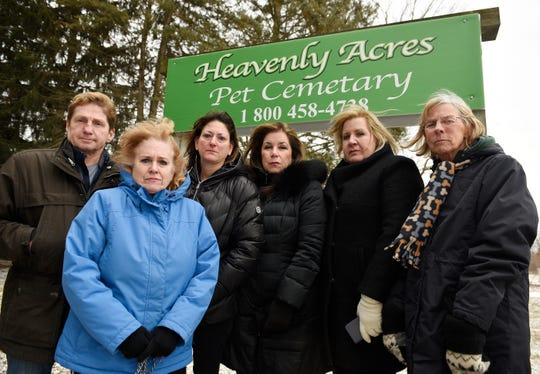 Pet owners, from left, Todd Golding, Carol Skurski, Kim Goldstein, Jill Daly, Diane Rousseau and Pat Mankin pose in front of of the entrance of Heavenly Acres Pet Cemetery in Howell.  They have been advised that they should exhume the bodies of their pets from the closed cemetery because the property is on the market to be sold.