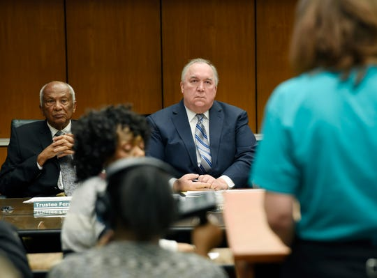 Interim President John Engler and trustee Joel Ferguson listen to a student during the public comment portion of Michigan State University's Board of Trustees meeting on Wed., Jan. 9, 2018 in East Lansing.