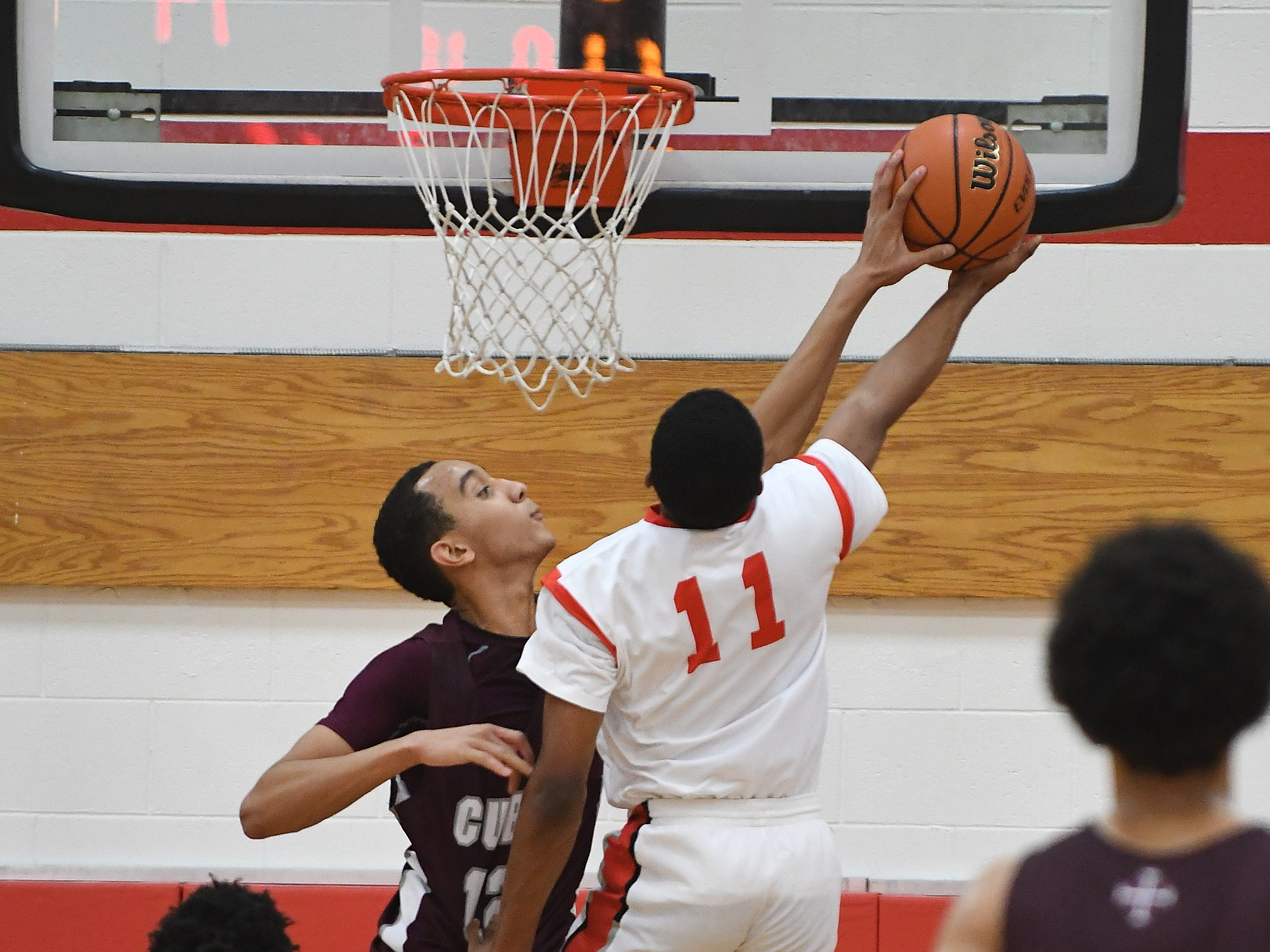 U-D Jesuit's J.T. Morgan blocks a shot by Lorne Bowman II of Orchard Lake St. Mary's in the first half.