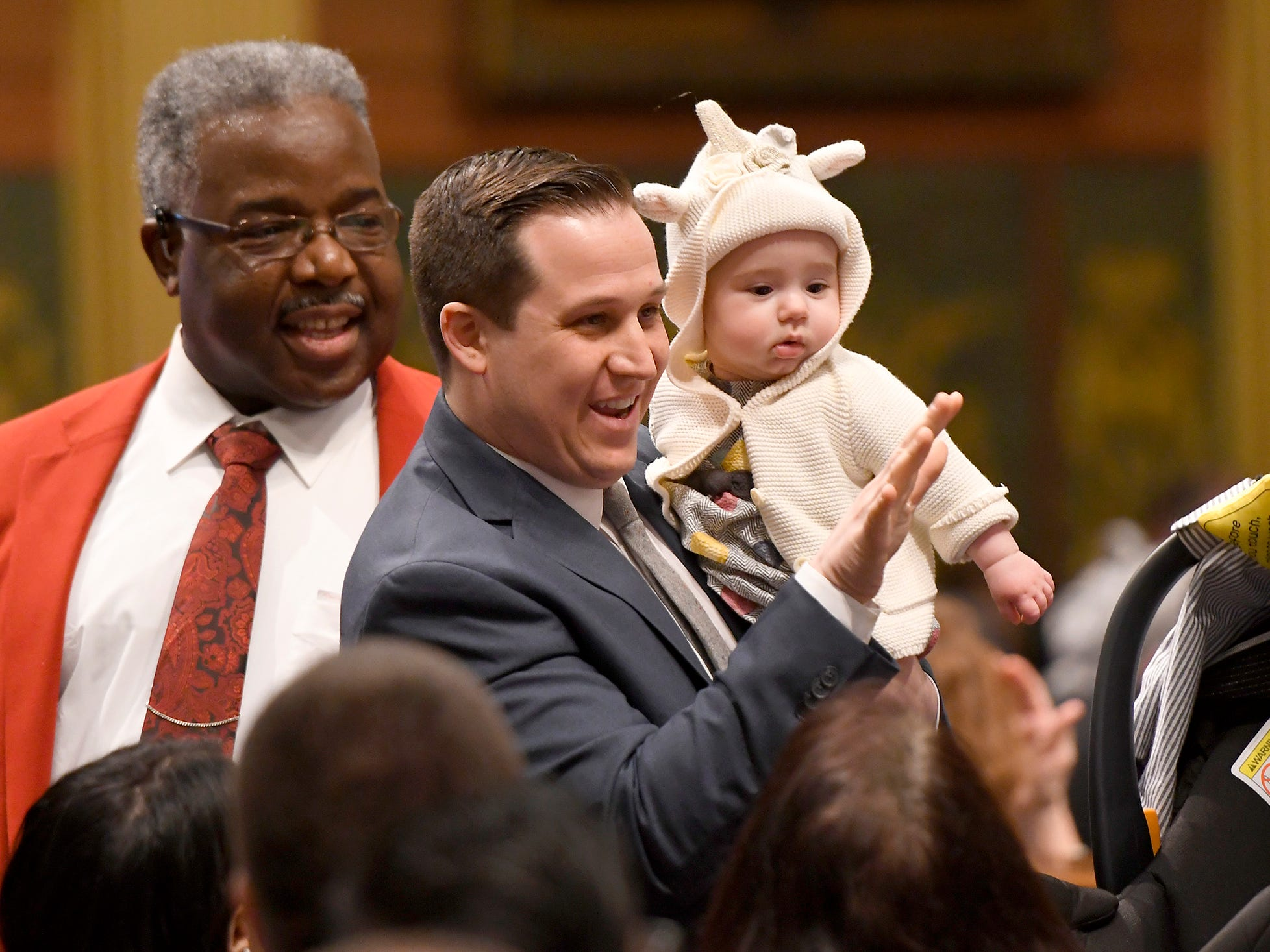 State Rep. Robert Wittenberg, D-27th District, waves to colleagues with daughter Ada, 6 months, before the opening  ceremonies.