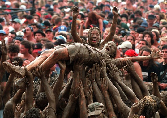 Mud-covered moshers cavort in front of the stage at the Woodstock '94 festival in Saugerties, New York, on Aug. 12, 1994 photo.