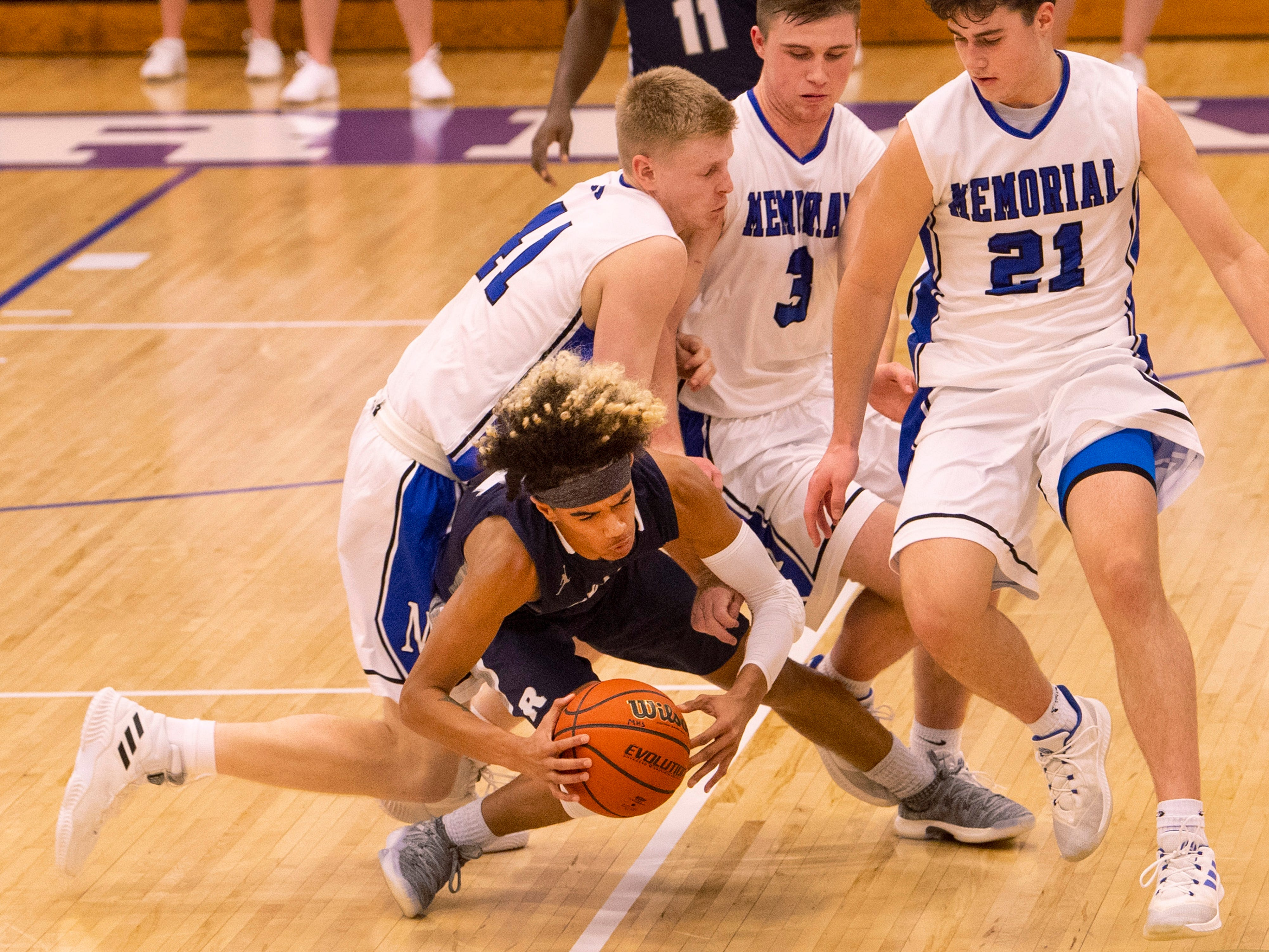 Reitz's Khristian Lander (4) is fouled hard after making a steal against Memorial in the first round of the SIAC Tournament at Memorial High School Tuesday night.