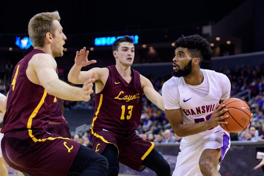 Loyola's Bruno Skokna (4) and Loyola's Clayon Custer (13) double team University of Evansville's K.J. Riley (33) as he looks to make a pass in the first half at Ford Center in Evansville, Ind., Tuesday, Jan. 8, 2019. The Purple Aces rolled over the Ramblers, 67-48.