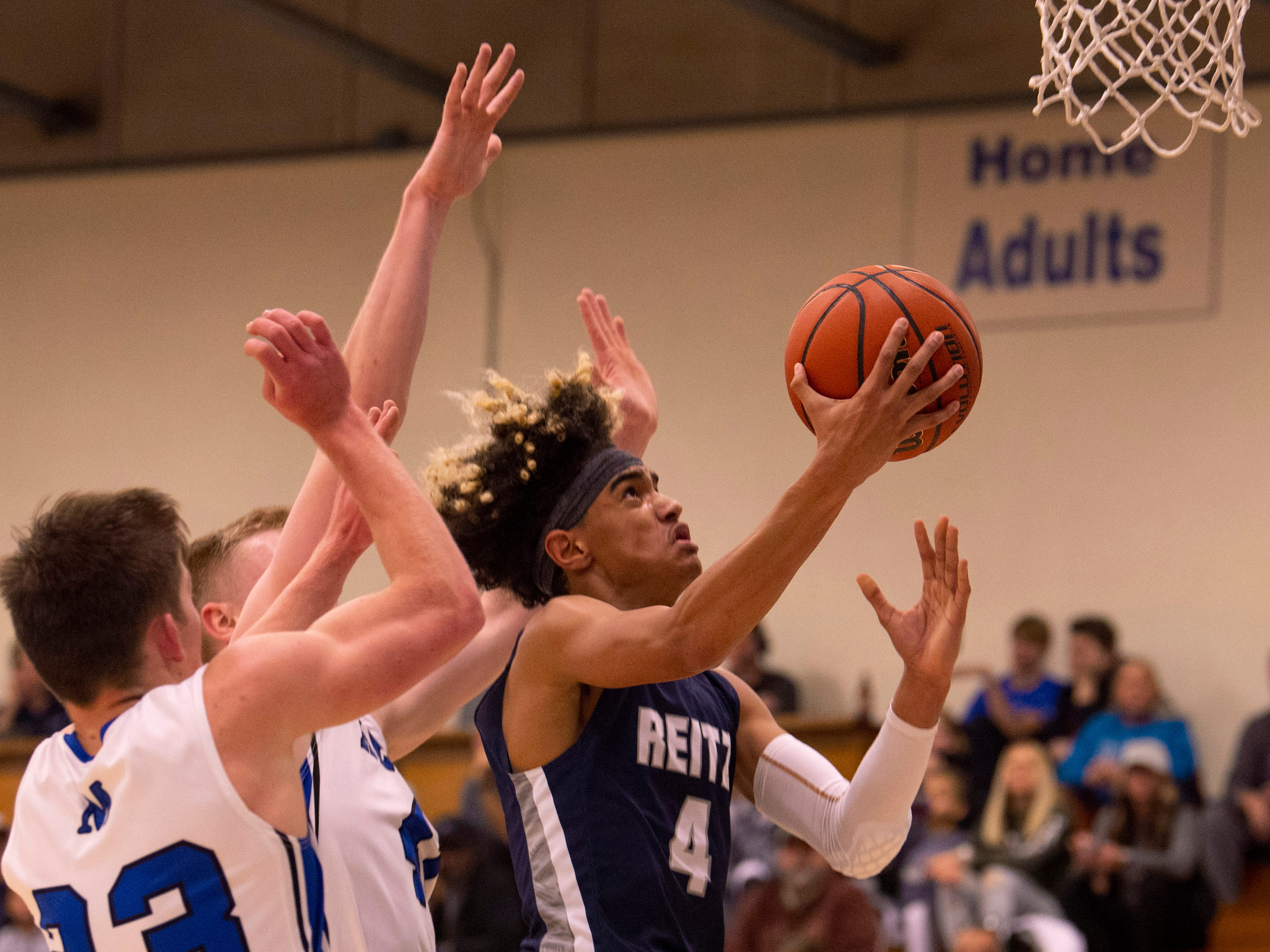 Reitz's Khristian Lander (4) shoots around Memorial's defense in the first round of the SIAC Tournament at Memorial High School Tuesday night.