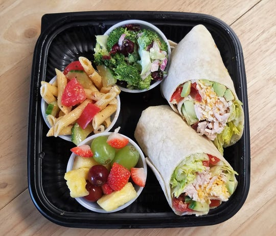 A turkey and cheddar wrap with avocado, accompanied by broccoli salad, fruit salad, and pasta salad at the Caboose.