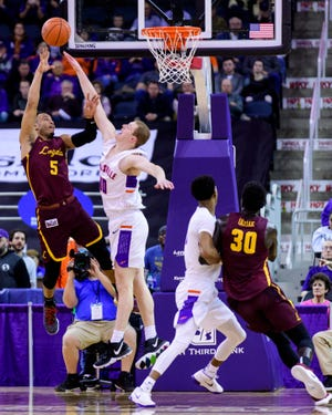 University of Evansville's Evan Kuhlman (10) blocks Loyola's Marques Townes (5) from the net in the first half at Ford Center in Evansville, Ind., Tuesday, Jan. 8, 2019. The Purple Aces rolled over the Ramblers, 67-48.