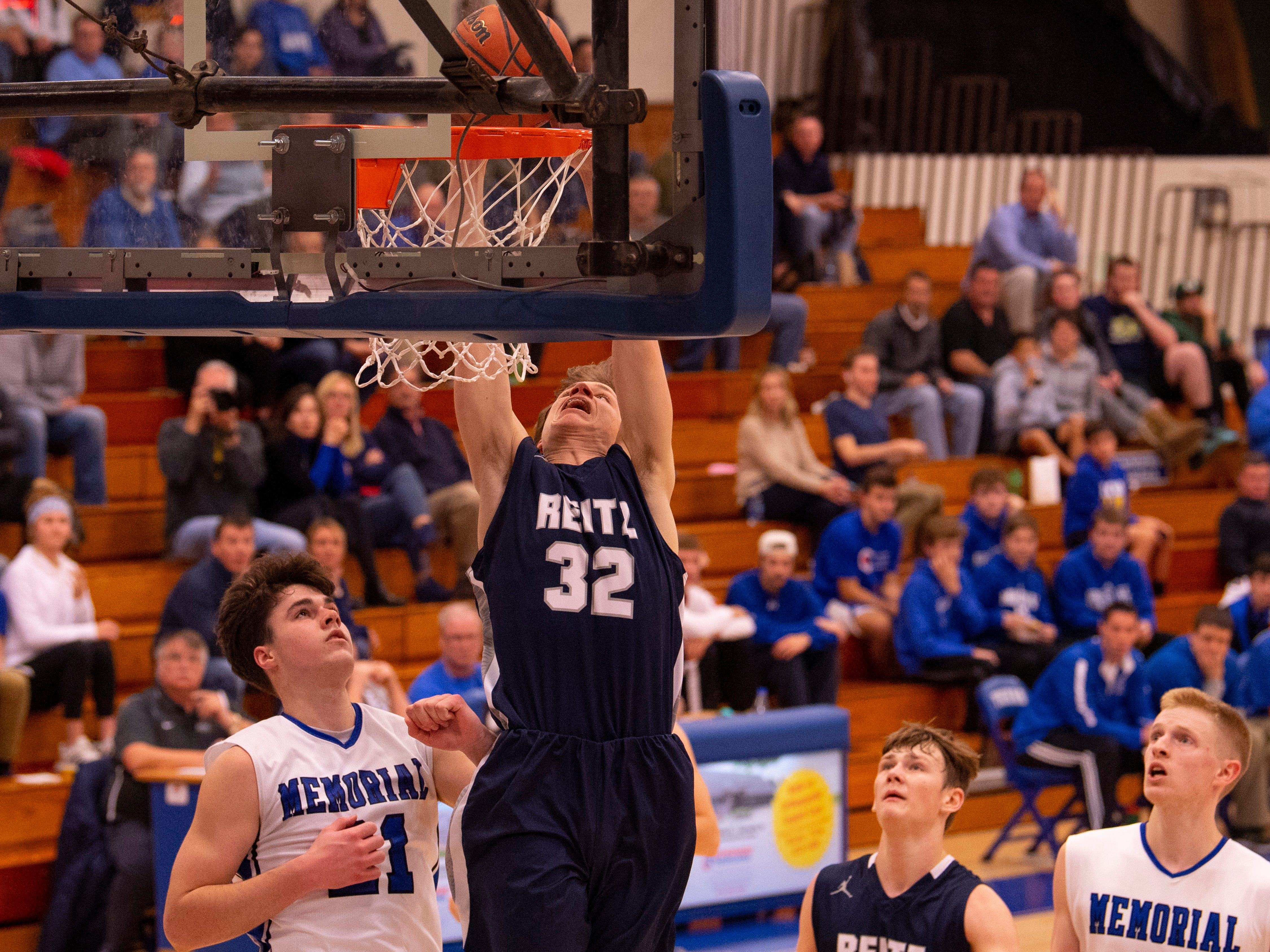 Reitz's Ethan Higgs (32) dunks against Memorial in the first round of the SIAC Tournament at Memorial High School Tuesday night.