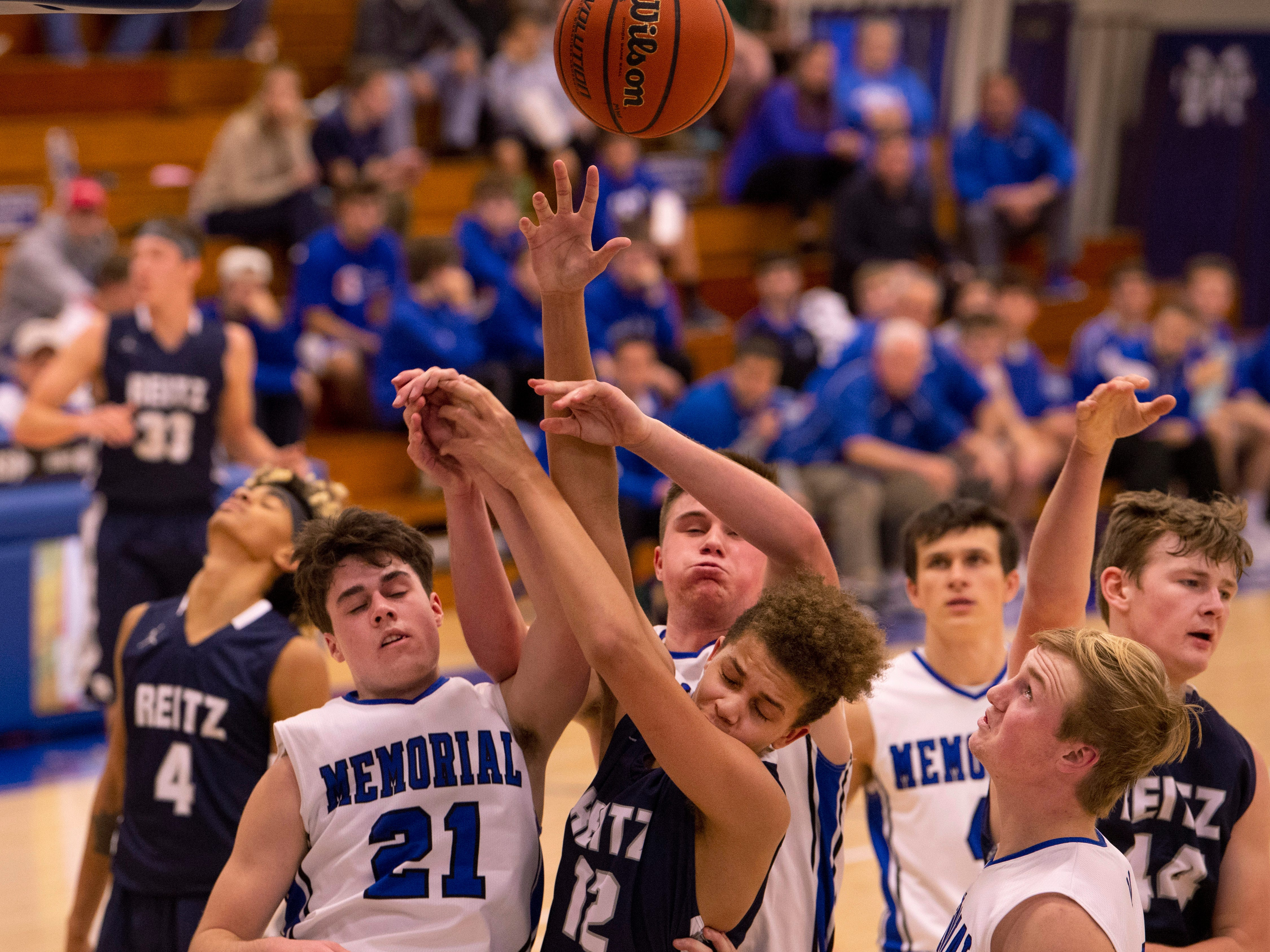 Memorial and Reitz go for a rebound in the first round of the SIAC Tournament at Memorial High School Tuesday night.
