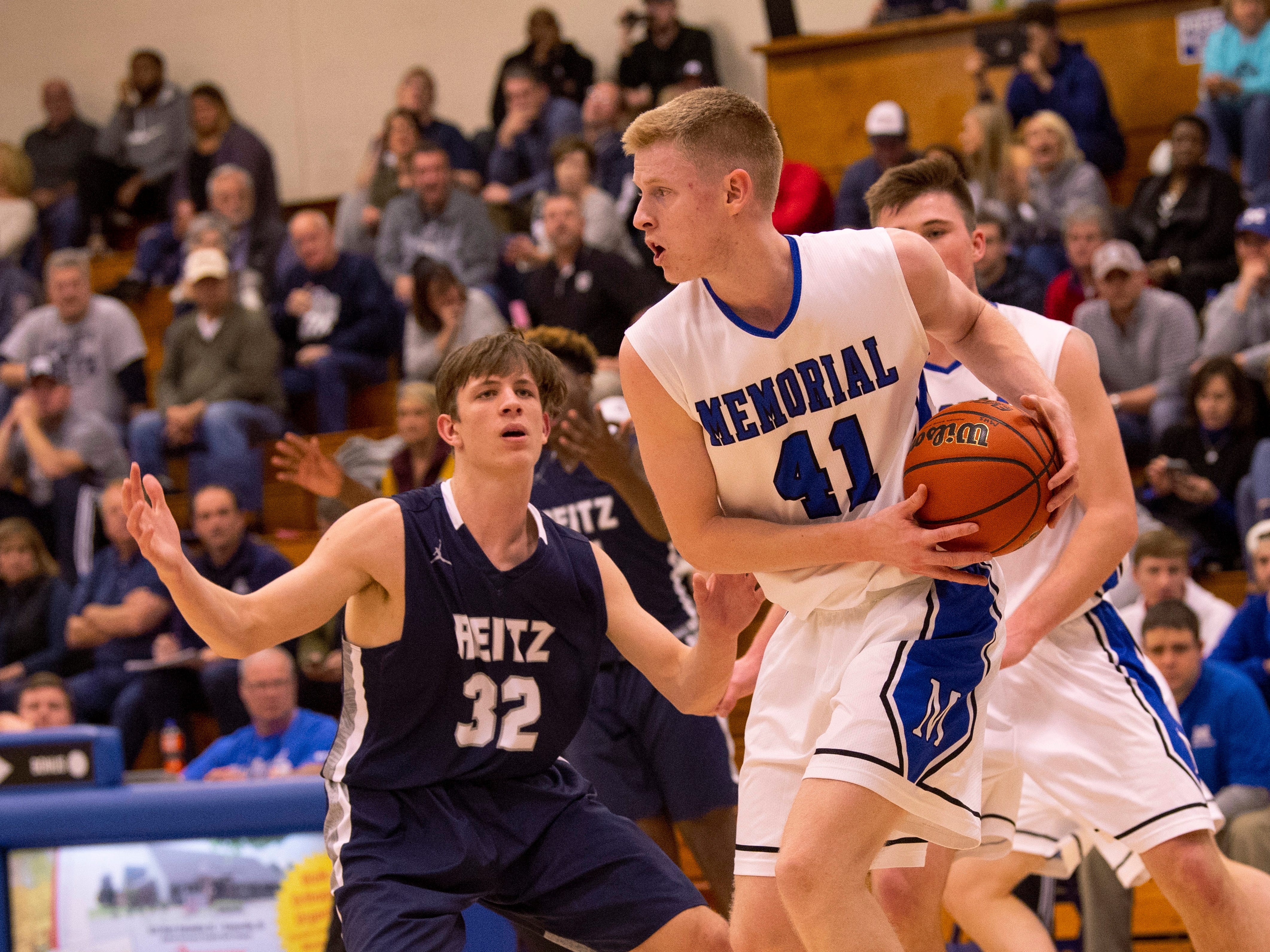 Reitz's Ethan Higgs (32) defends Memorial's Sam DeVault (41) in the first round of the SIAC Tournament at Memorial High School Tuesday night.