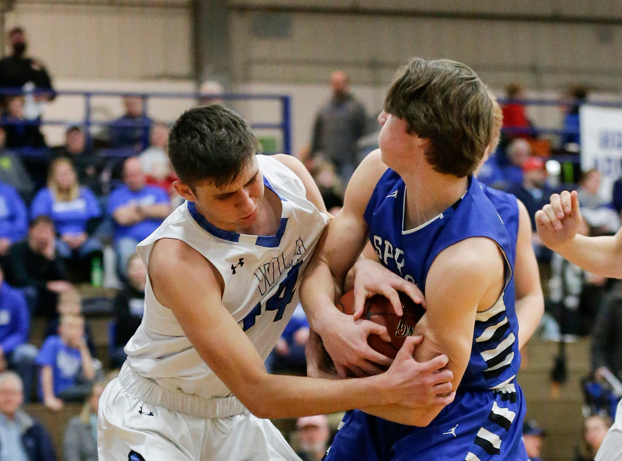 Winnebago Lutheran Academy boys basketball's Benji Cole and St. Mary's Springs Academy's Cade Christensen battle for the ball Tuesday, Jan. 8, 2019, during their game in Fond du Lac. Winnebago Lutheran Academy won the game 69-66.