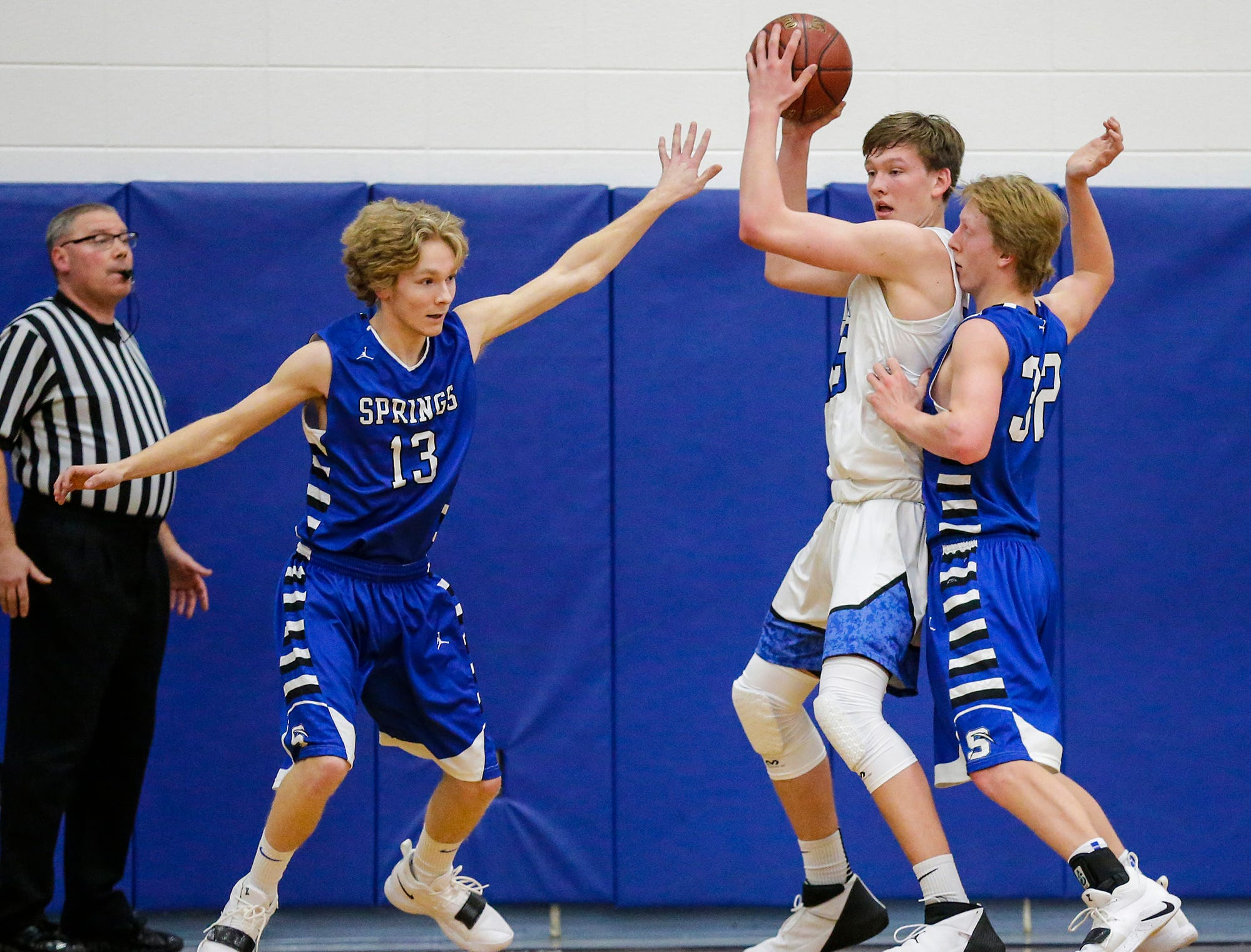 St. Mary's Spring Academy boys basketball's Myles Ottery (13) and Ezra Tucker (32) defend against Winnebago Lutheran Academy's Gabe Pruss Tuesday, Jan. 8, 2019, during their game in Fond du Lac. Winnebago Lutheran Academy won the game 69-66.