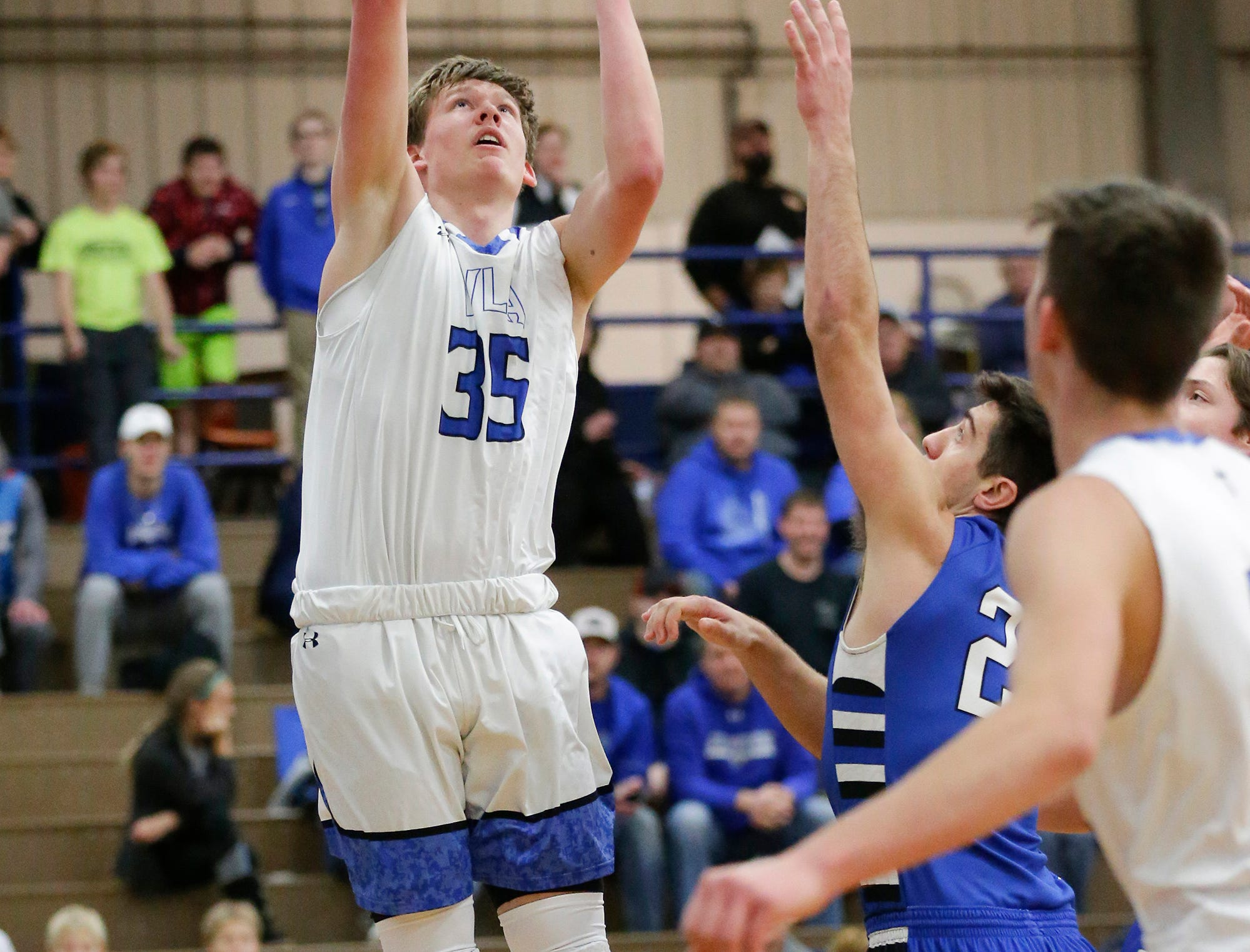 Winnebago Lutheran Academy boys basketball's Gabe Pruss goes up for a shot over St. Mary's Springs Academy's Justin Ditter Tuesday, Jan. 8, 2019, during their game in Fond du Lac. Winnebago Lutheran Academy won the game 69-66.