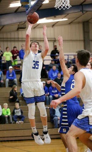 Winnebago Lutheran boys basketball player Gabe Pruss goes up for a shot over St. Mary's Springs Academy's Justin Ditter on Tuesday in Fond du Lac.