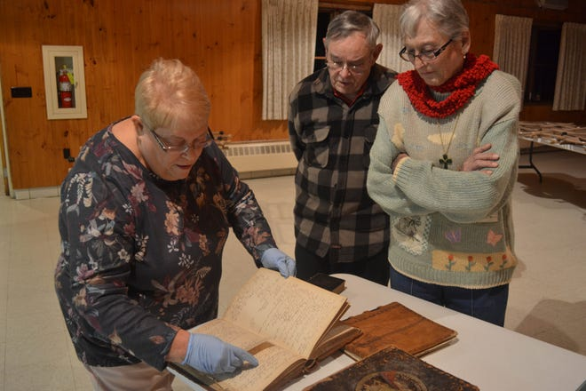 Connie Carnicom scans through entries in the church's original membership book as Ron Claypool and Rosie Reno look on.