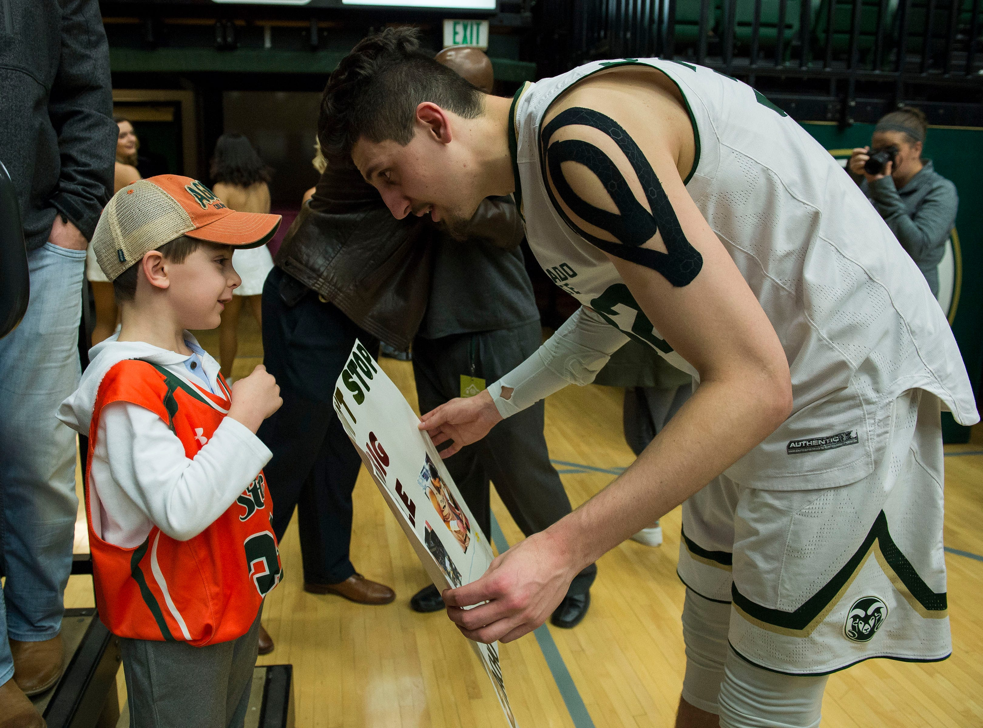 Colorado State University junior center Nico Carvacho (32) receives a home-made poster from a young fan after a game against the Air Force Academy on Tuesday, Jan. 8, 2019, at Moby Arena in Fort Collins, Colo.
