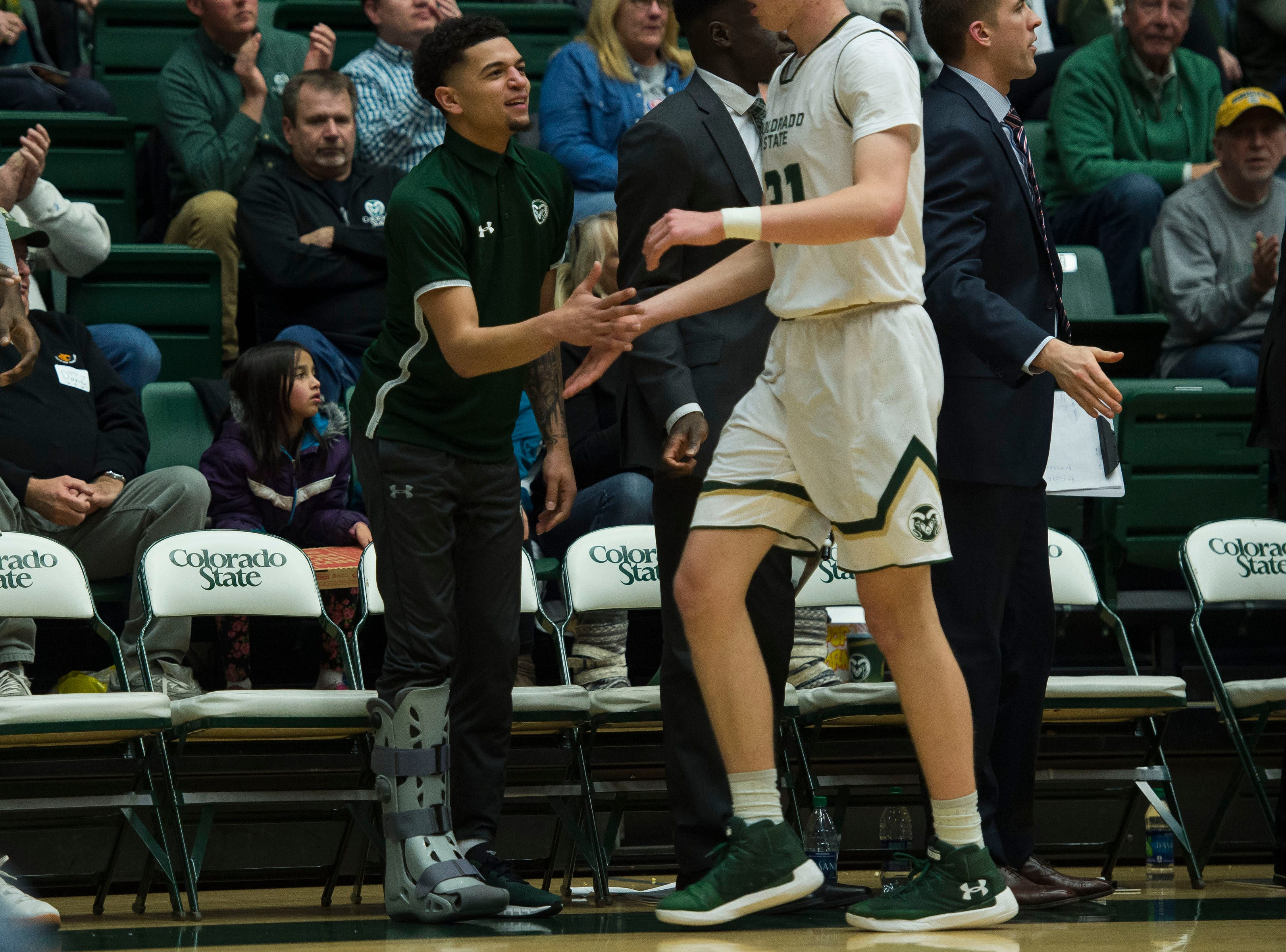 Colorado State University junior guard Anthony Masinton-Bonner (15) greets freshman forward Adam Thistlewood (31) while wearing a boot on the bench during a game against  Air Force Academy on Tuesday, Jan. 8, 2019, at Moby Arena in Fort Collins, Colo.