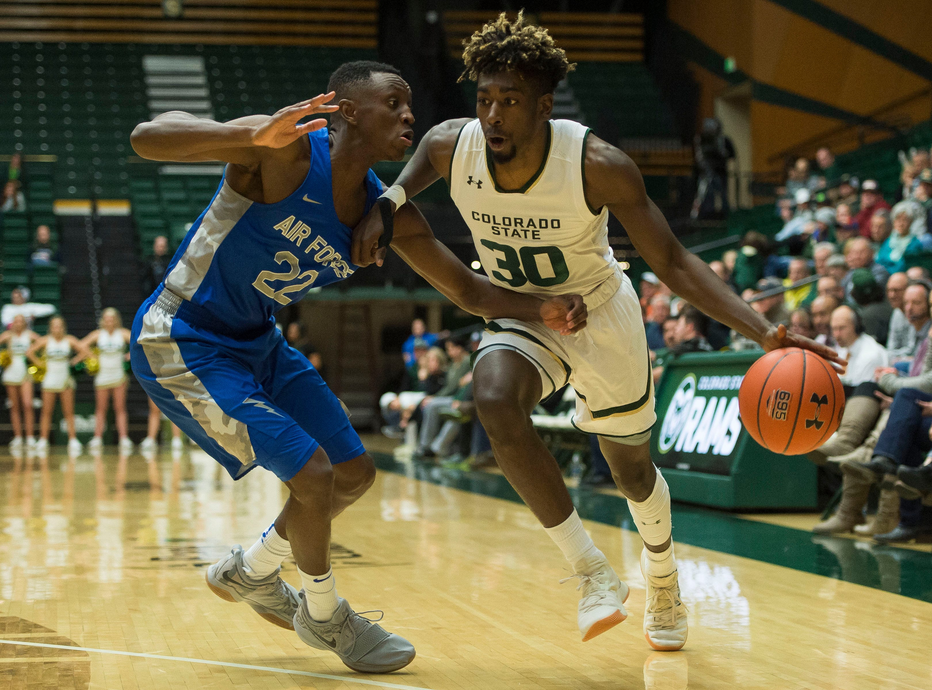 Colorado State University junior guard Kris Martin (30) drives past Air Force Academy senior guard PErvis Louder (22) on Tuesday, Jan. 8, 2019, at Moby Arena in Fort Collins, Colo.