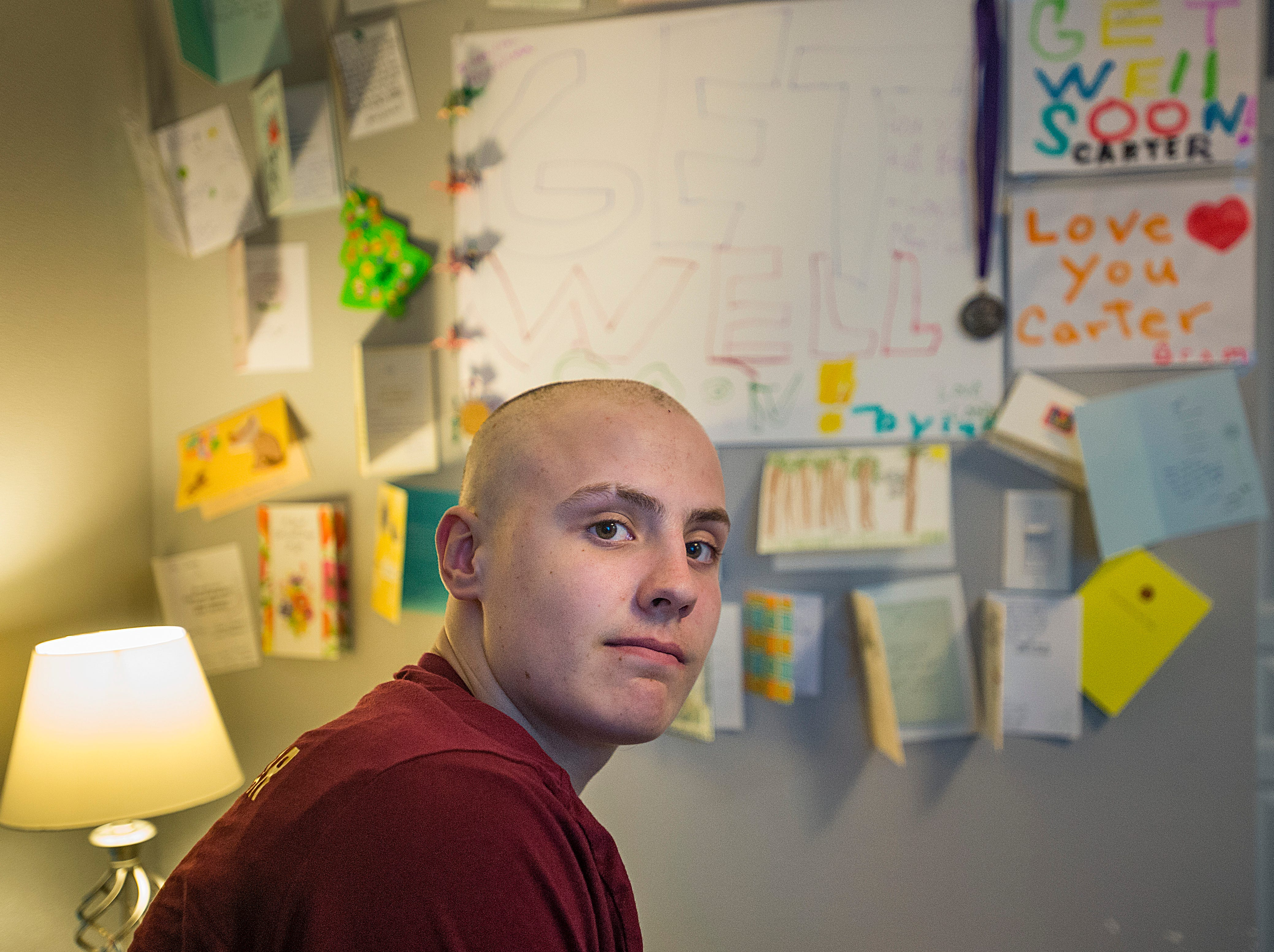 Carter Edgerley, 17, poses for a photo in front of the many cards showing support for his fight against cancer in his room on Tuesday, January 8, 2019.