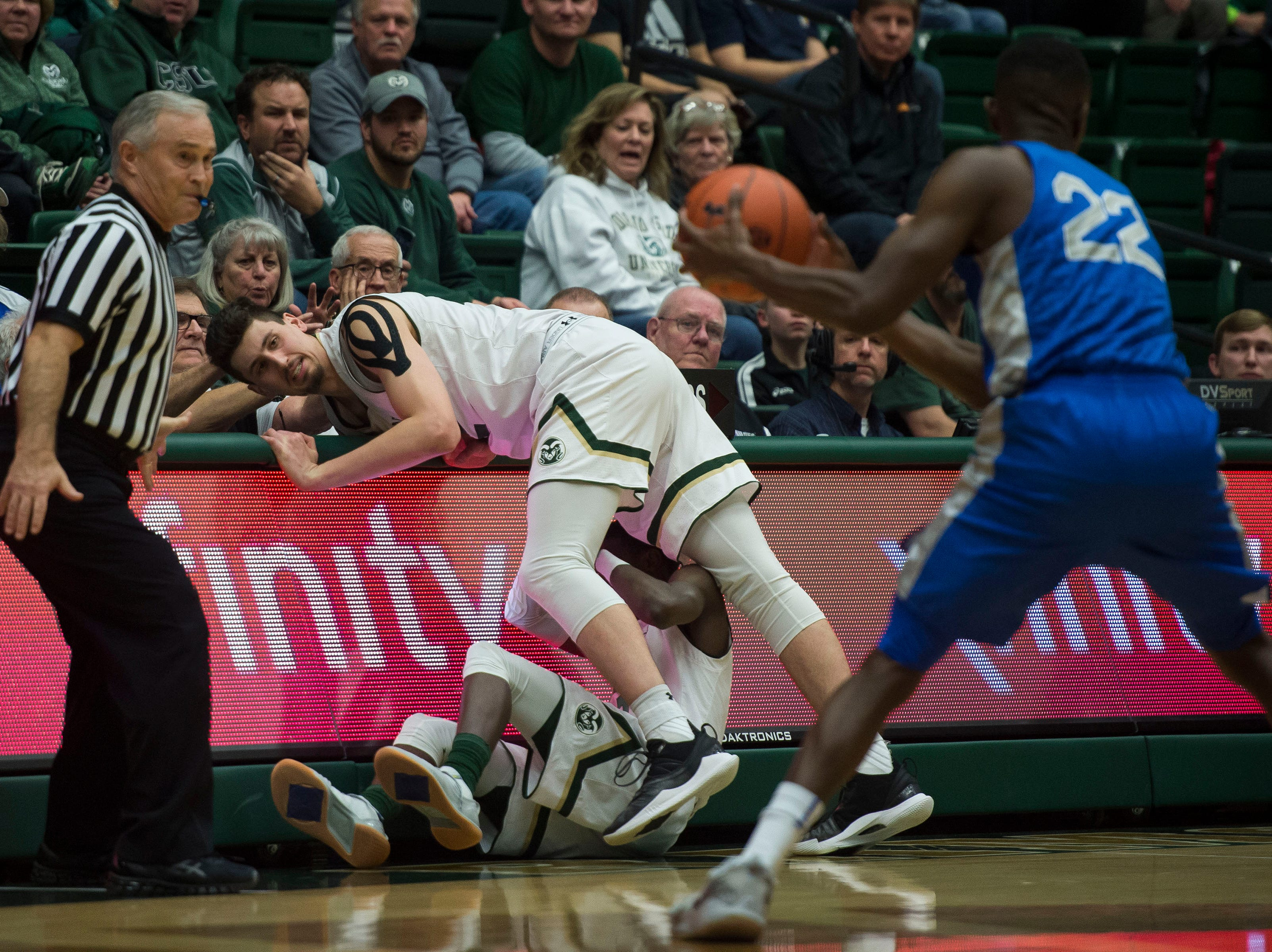 Colorado State University junior center Nico Carvacho (32) runs into freshman teammate Kendle Moore (3) after loosing control of the ball to Air Force Academy senior guard Pervis Louder (22) on Tuesday, Jan. 8, 2019, at Moby Arena in Fort Collins, Colo.