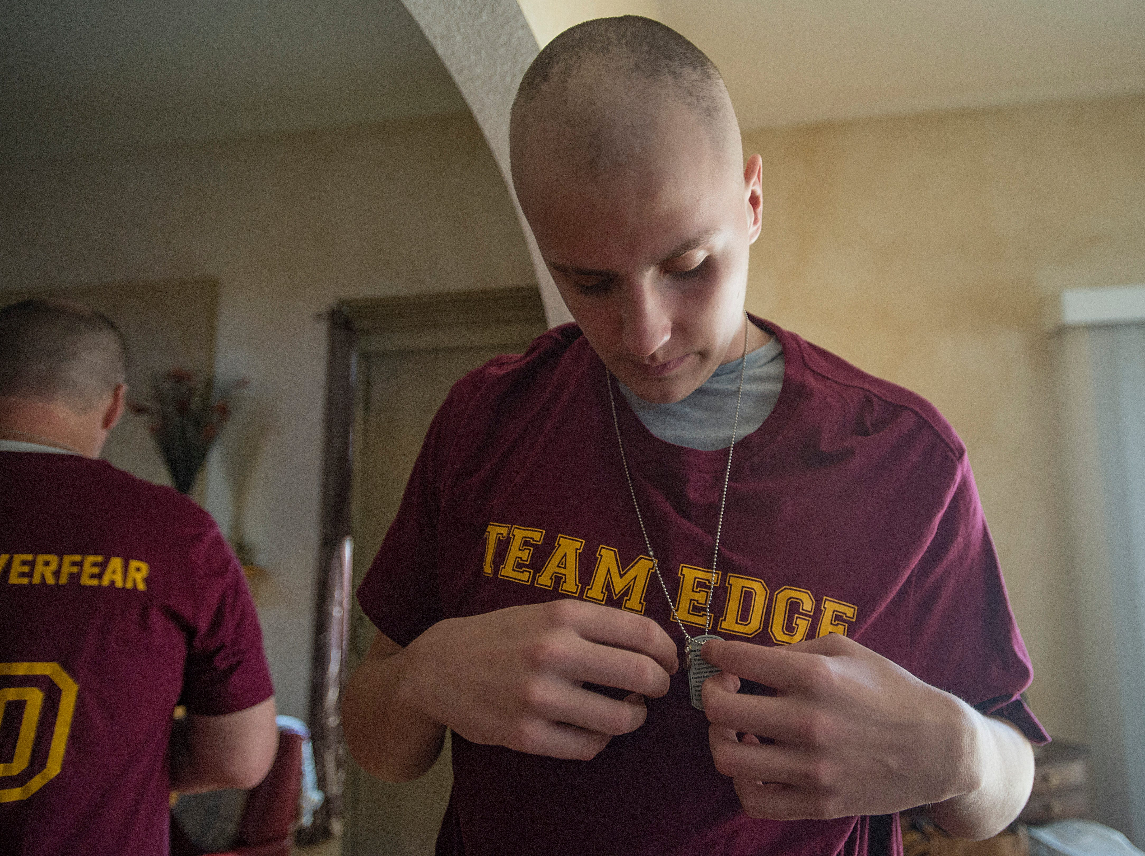 Carter Edgerley, 17, adjusts a dog tag around his neck at his home in Fort Collins on Tuesday, January 8, 2019. Edgerley and his family have been wearing the tags with positive messages on fighting cancer inscribed on them.