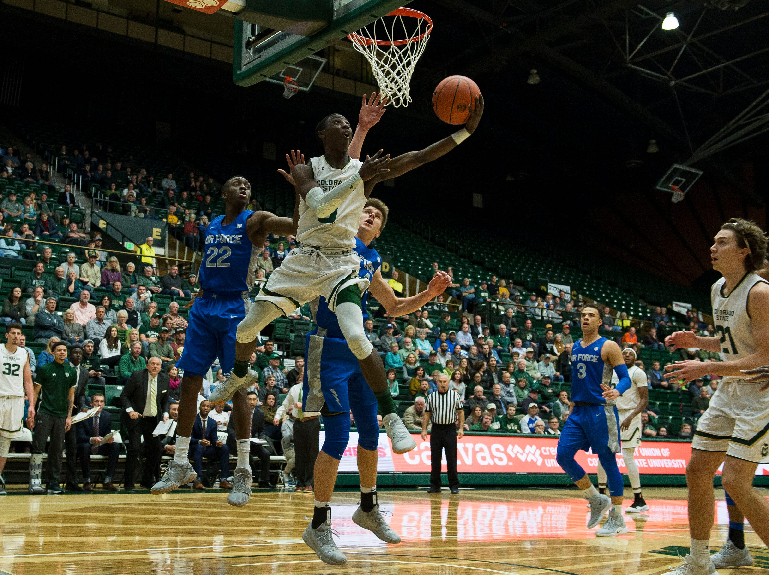 Colorado State University freshman guard Kendle Moore (3) goes under the net for a layup past Air Force Academy sophomore guard Keaton Van Soelen (44) on Tuesday, Jan. 8, 2019, at Moby Arena in Fort Collins, Colo.
