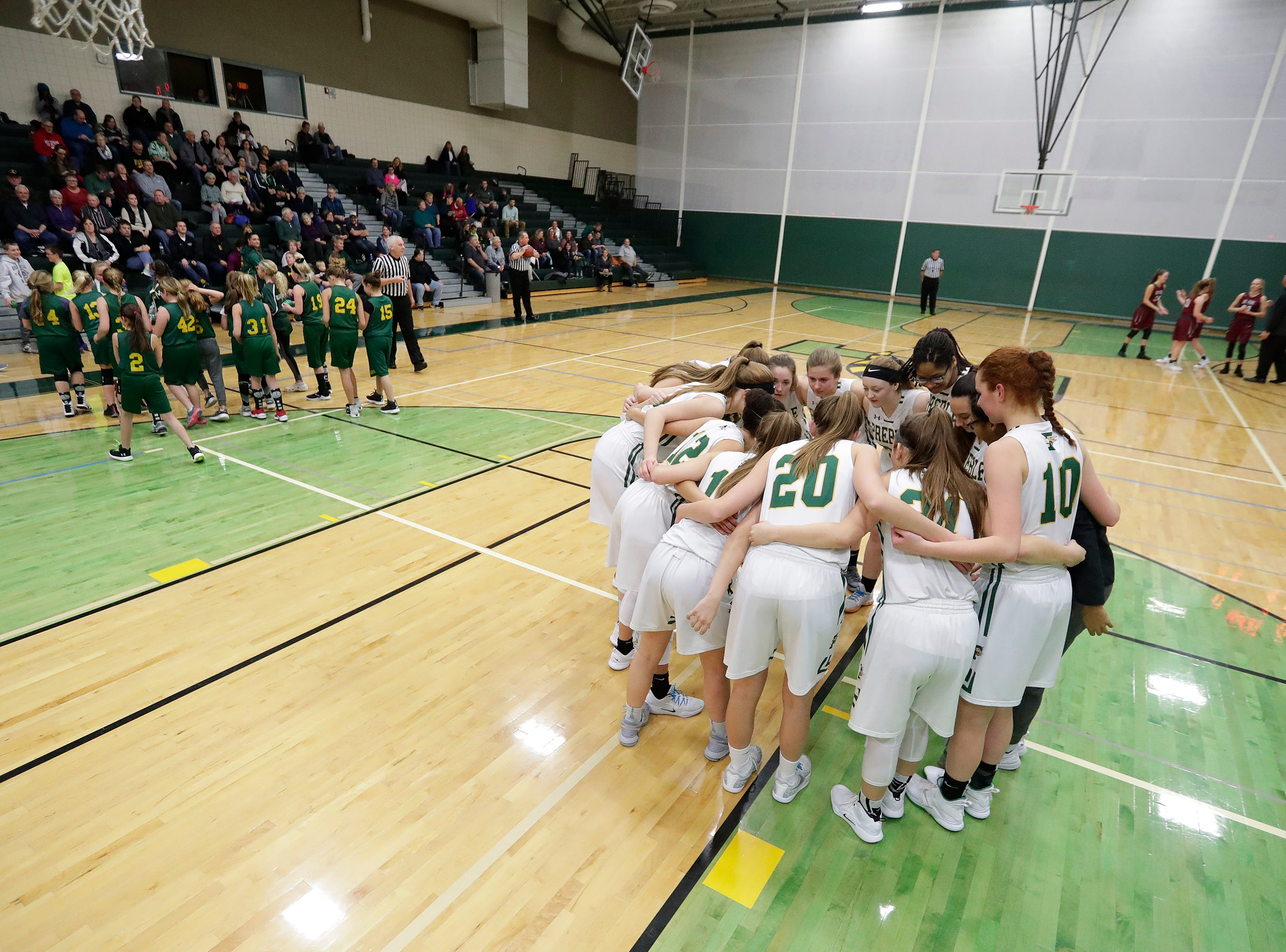 Green Bay Preble players huddle before facing De Pere in a girls basketball game at Preble high school on Tuesday, January 8, 2019 in Green Bay, Wis.