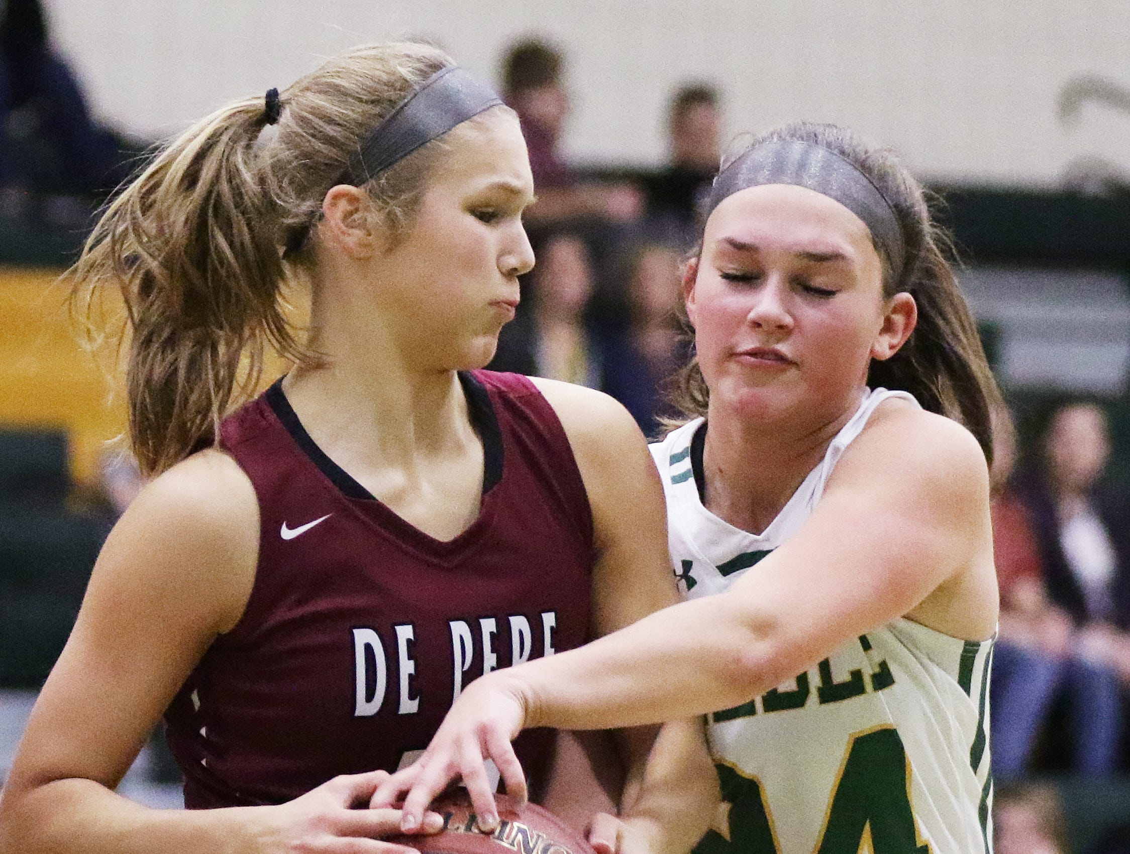 Green Bay Preble's Ella Bialkowski (24) fights for a rebound against De Pere's Keely Dorn (13) in a girls basketball game at Preble high school on Tuesday, January 8, 2019 in Green Bay, Wis.