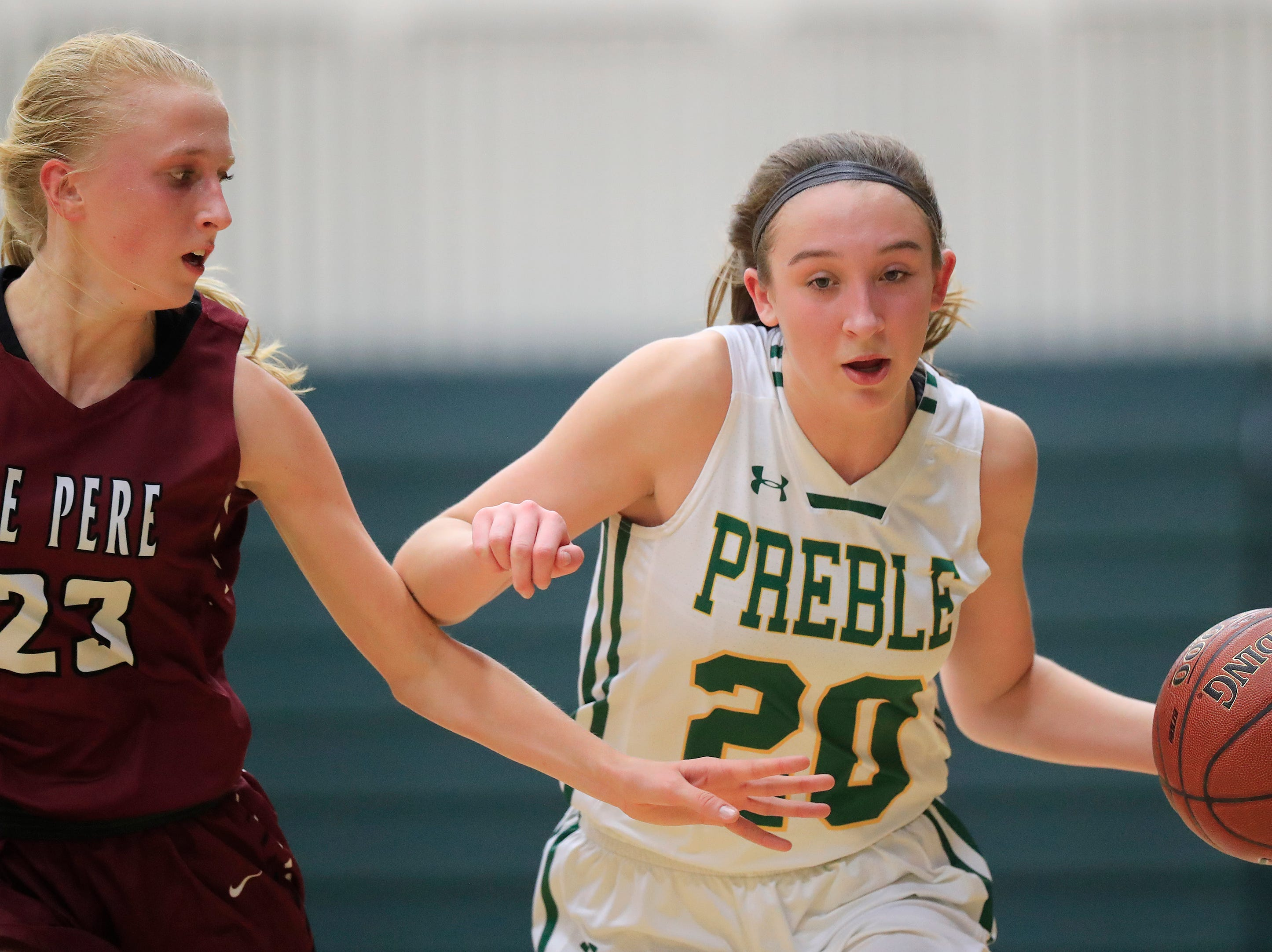 Green Bay Preble's Carley Duffney (20) dribbles against De Pere's Jordan Meulemans (23) in a girls basketball game at Preble high school on Tuesday, January 8, 2019 in Green Bay, Wis.