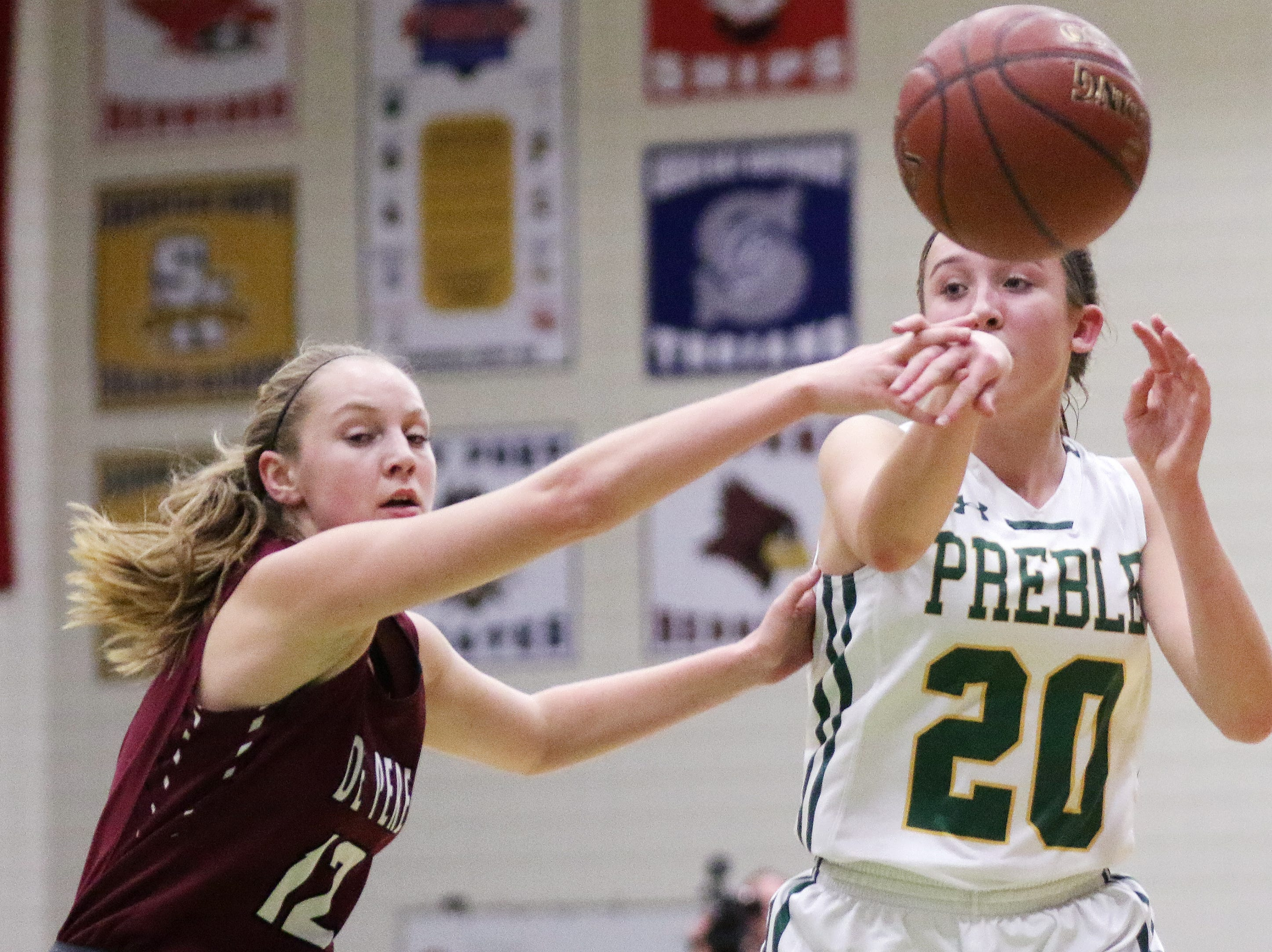 Green Bay Preble's Carley Duffney (20) passes out of pressure from De Pere's Elena Miller (12) in a girls basketball game at Preble high school on Tuesday, January 8, 2019 in Green Bay, Wis.