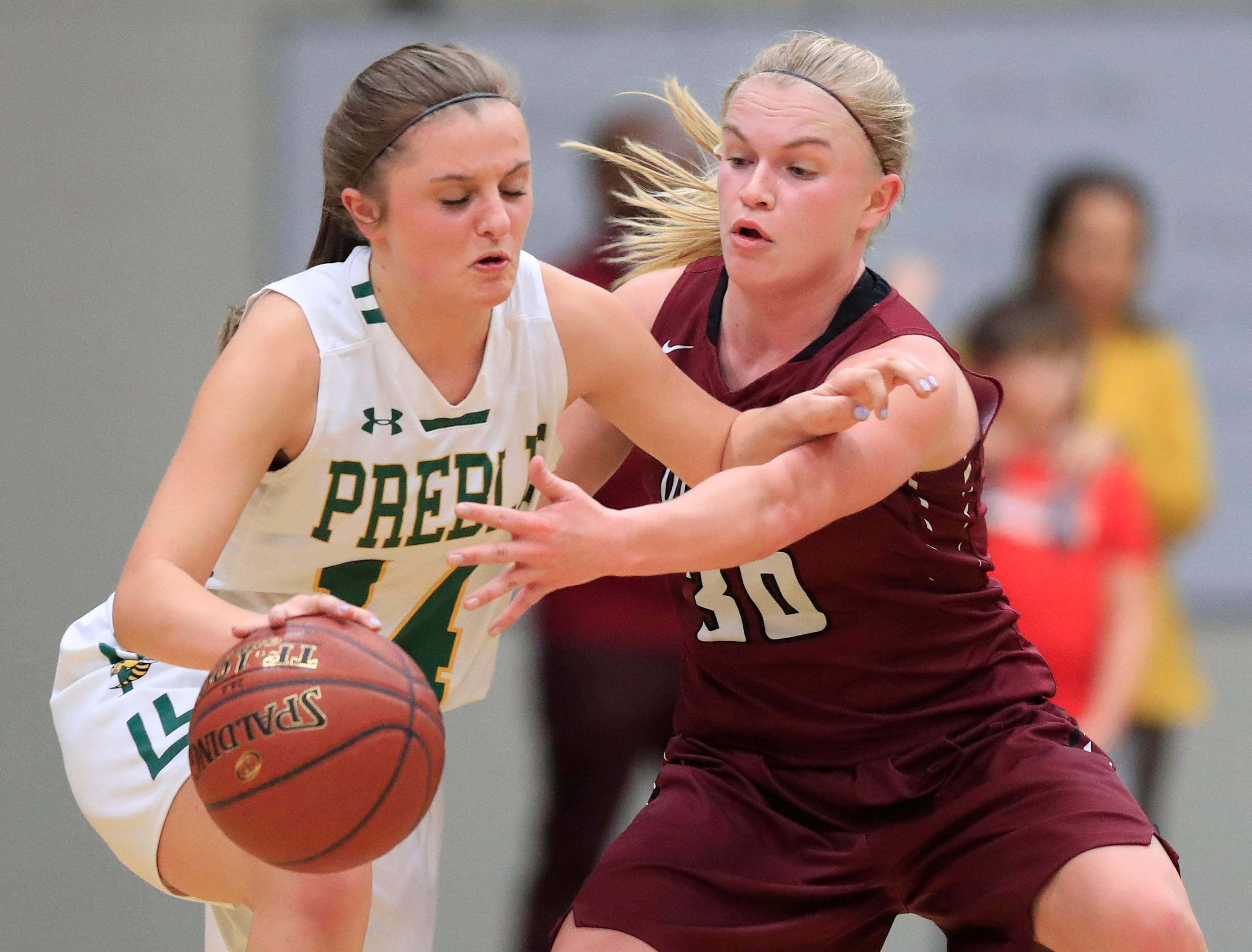 Green Bay Preble's Taylor Sleger (14) dribbles away from De Pere's Rachel Kerkhoff (30) in a girls basketball game at Preble high school on Tuesday, January 8, 2019 in Green Bay, Wis.