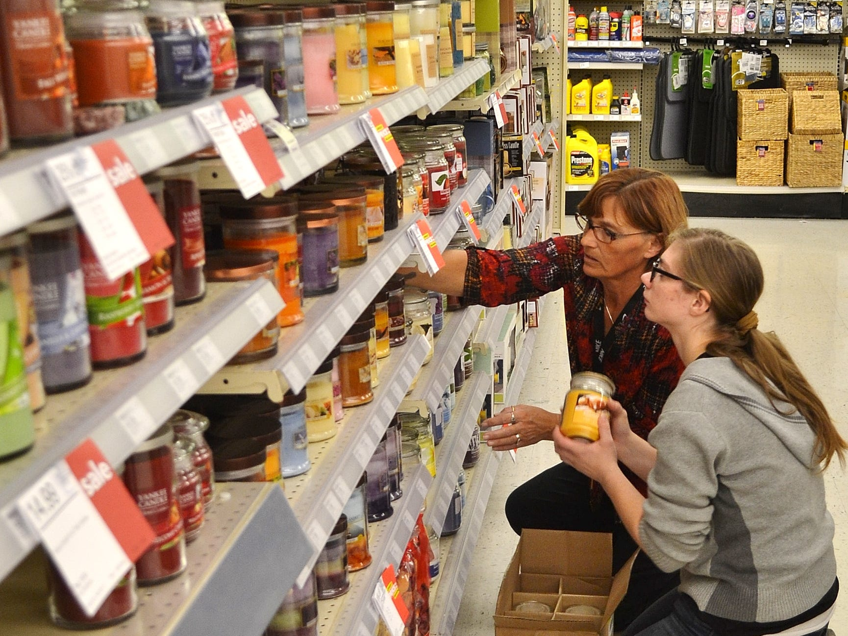 Shopko Hometown assistant manager Sandi Reed works with Oconto High School student Courtney Fager on stocking shelves of candles.