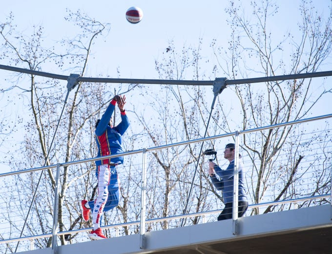 "Harlem Globetrotter Chandler ""Bulldog"" Mack makes a basket off of the Liberty Bridge at Falls Park on the Reedy  while filming a promotional video Wednesday, Jan. 9, 2019."