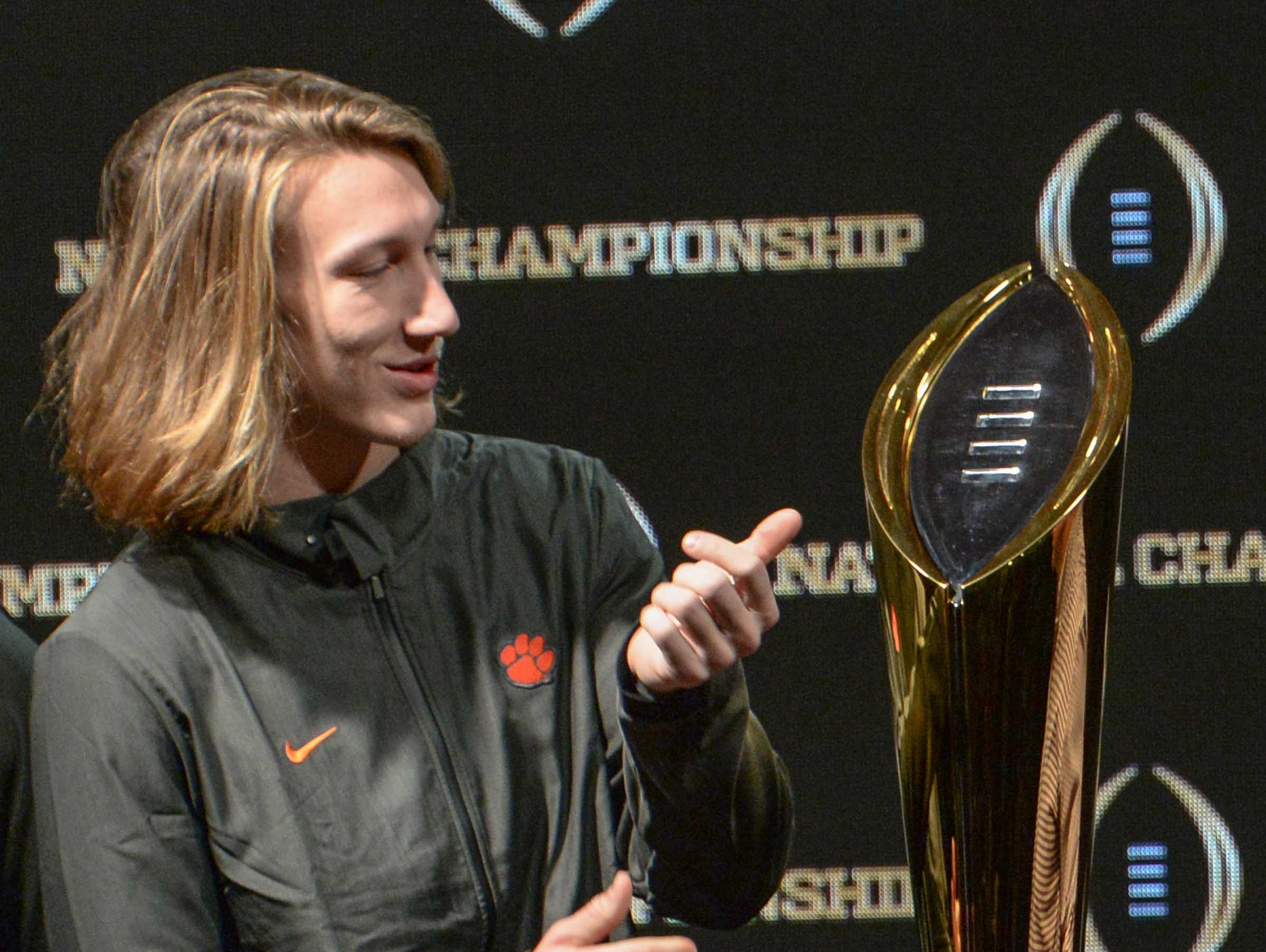 Clemson quarterback Trevor Lawrence stands near the championship trophy during the champions press conference the day after the College Football Championship in San Jose, California Tuesday, January 8, 2019.