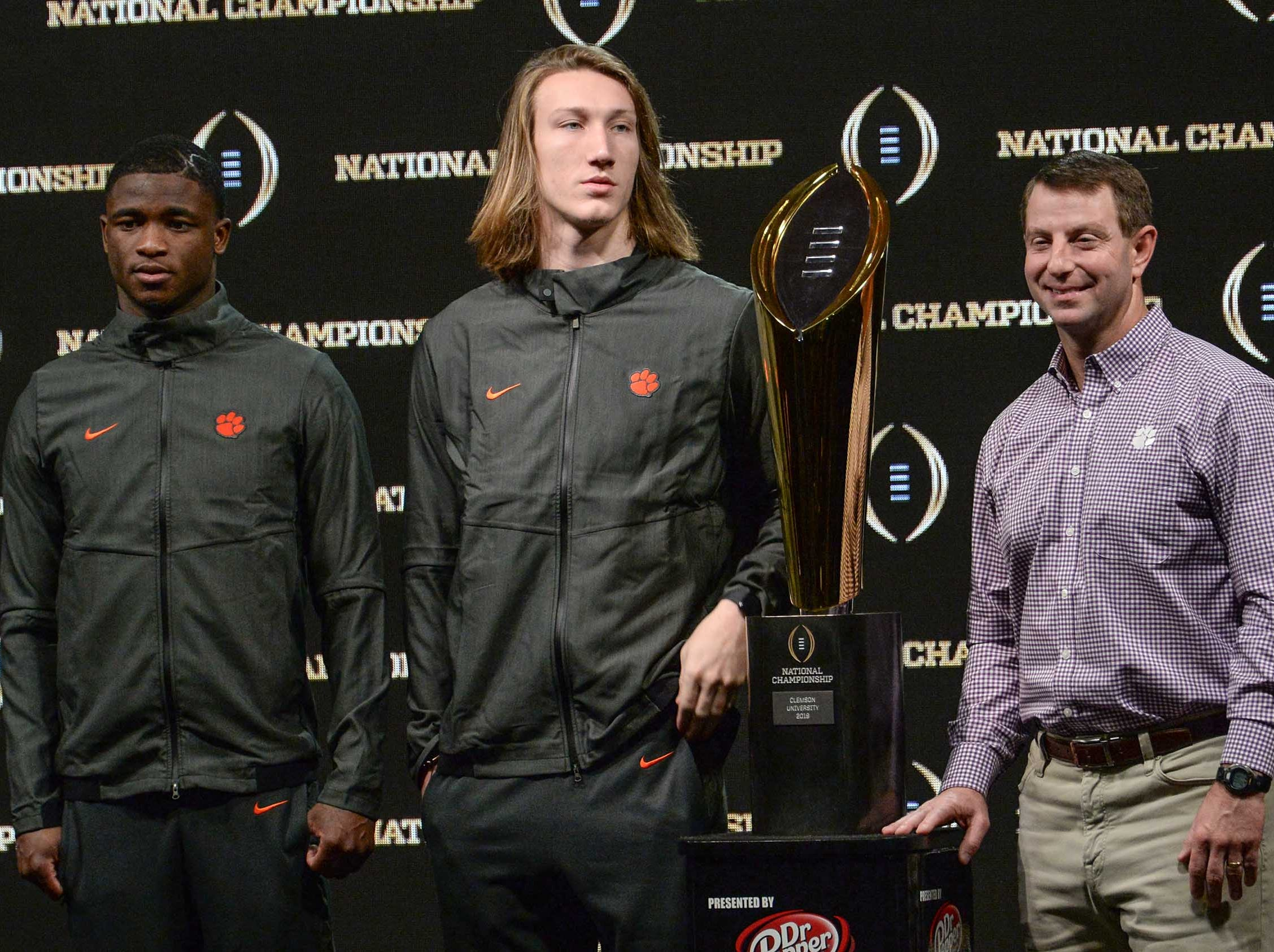 Clemson cornerback Trayvon Mullen, left, quarterback Trevor Lawrence and Head Coach Dabo Swinney stand near the championship trophy during the champions press conference the day after the College Football Championship in San Jose, California Tuesday, January 8, 2019.