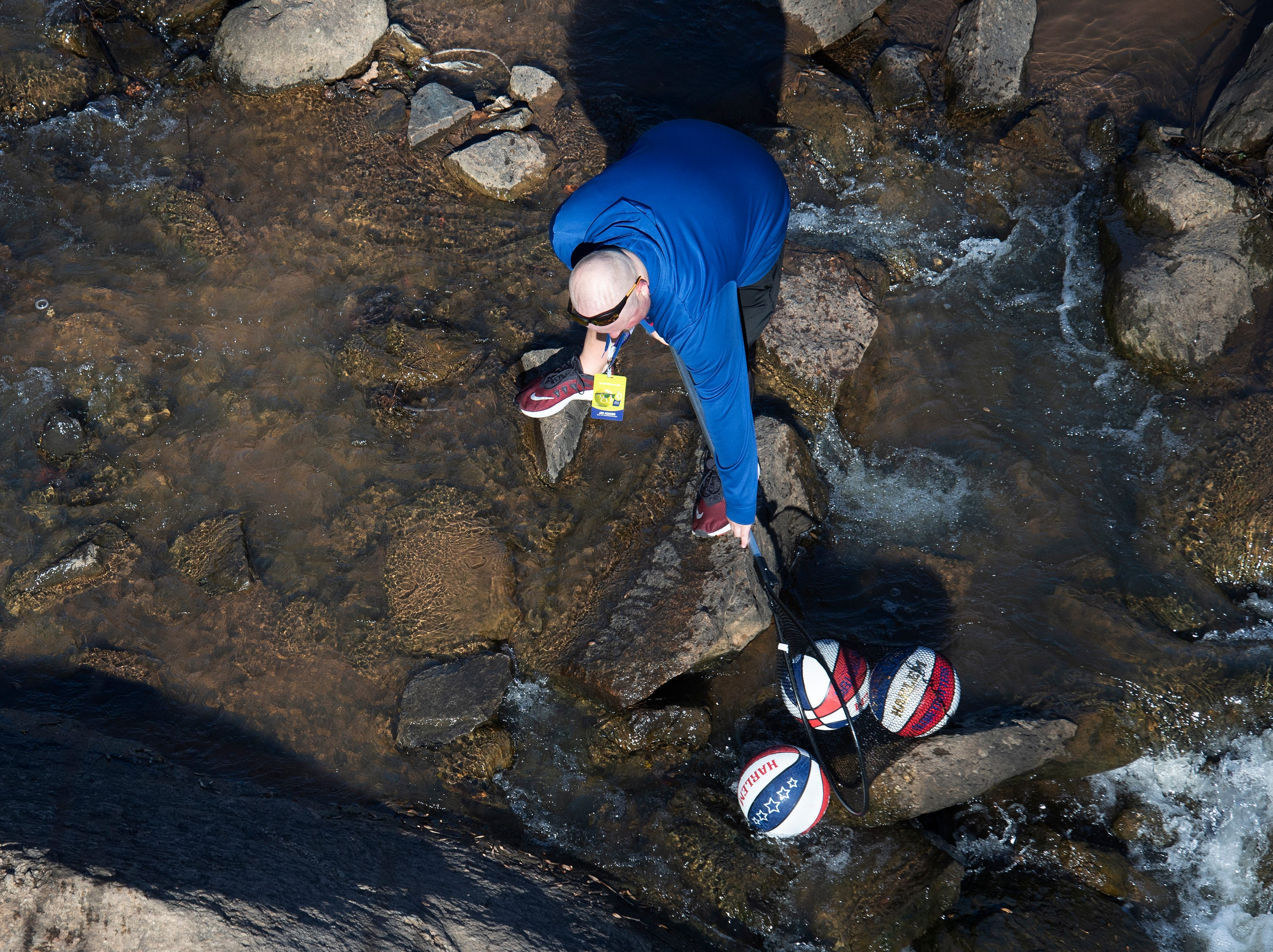 "Jay Adams, social media content manager for VisitGreenvilleSC, collects rogue basketballs while Harlem Globetrotter Chandler ""Bulldog"" Mack tries to make a basket off of the Liberty Bridge at Falls Park on the Reedy  while filming a promotional video Wednesday, Jan. 9, 2019."