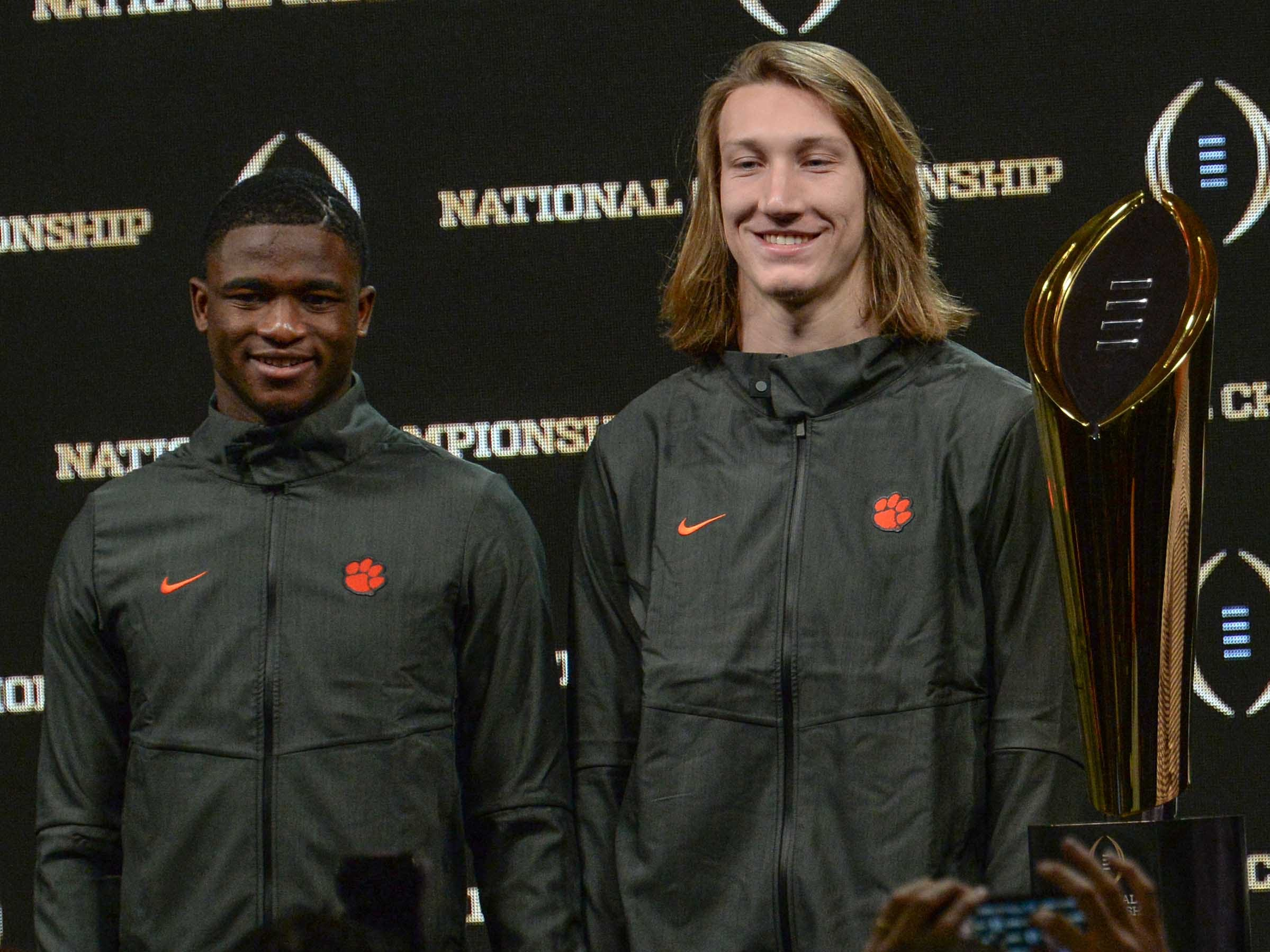Clemson cornerback Trayvon Mullen, left, and quarterback Trevor Lawrence stand near the championship trophy during the champions press conference the day after the College Football Championship in San Jose, California Tuesday, January 8, 2019.