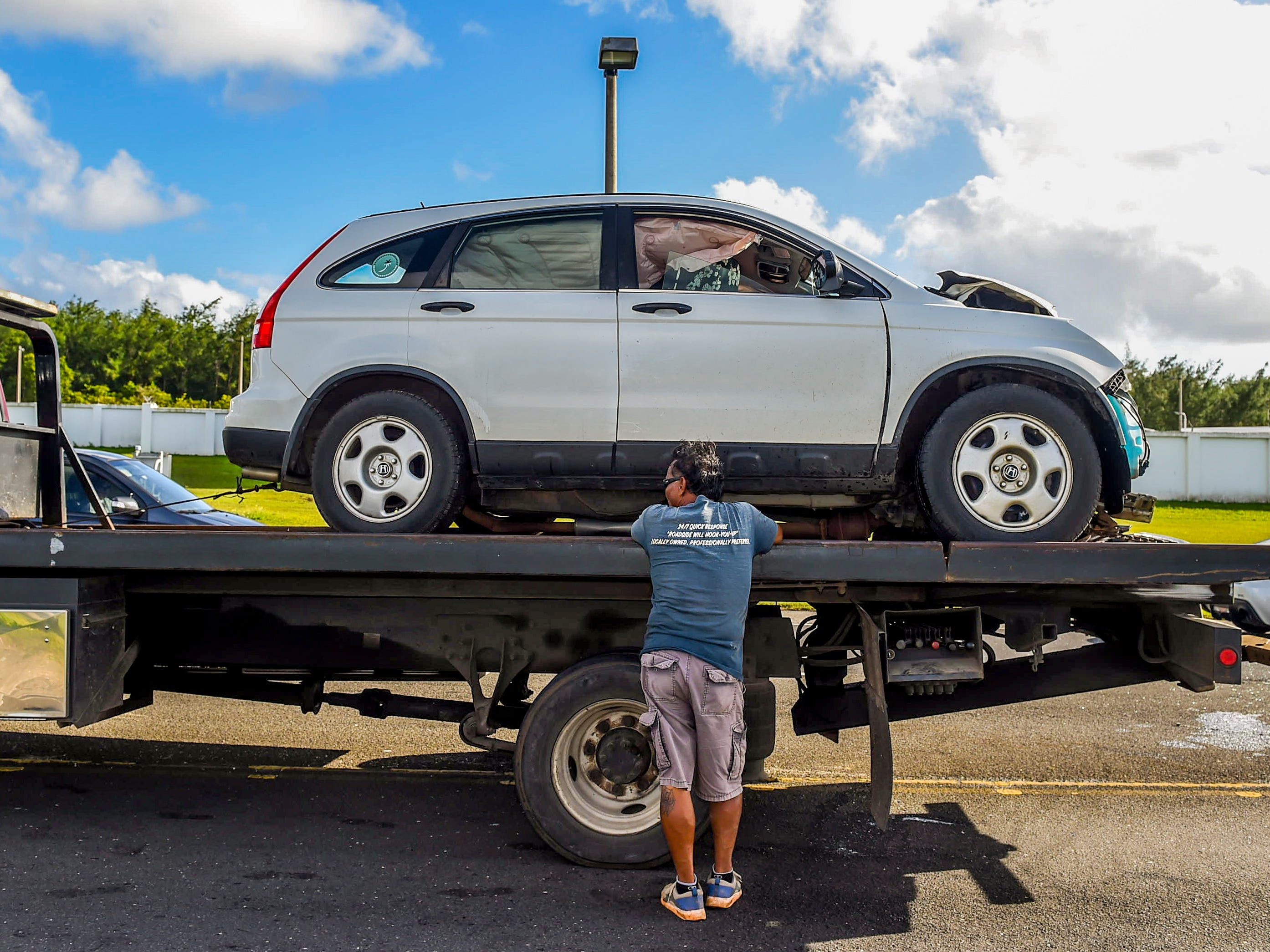 A Honda CR-V sports utility vehicle can be seen loaded on a vehicle transport as Guam Police Department officers conduct an investigation of a crash on Route 10A in Barrigada, Jan. 6, 2019.