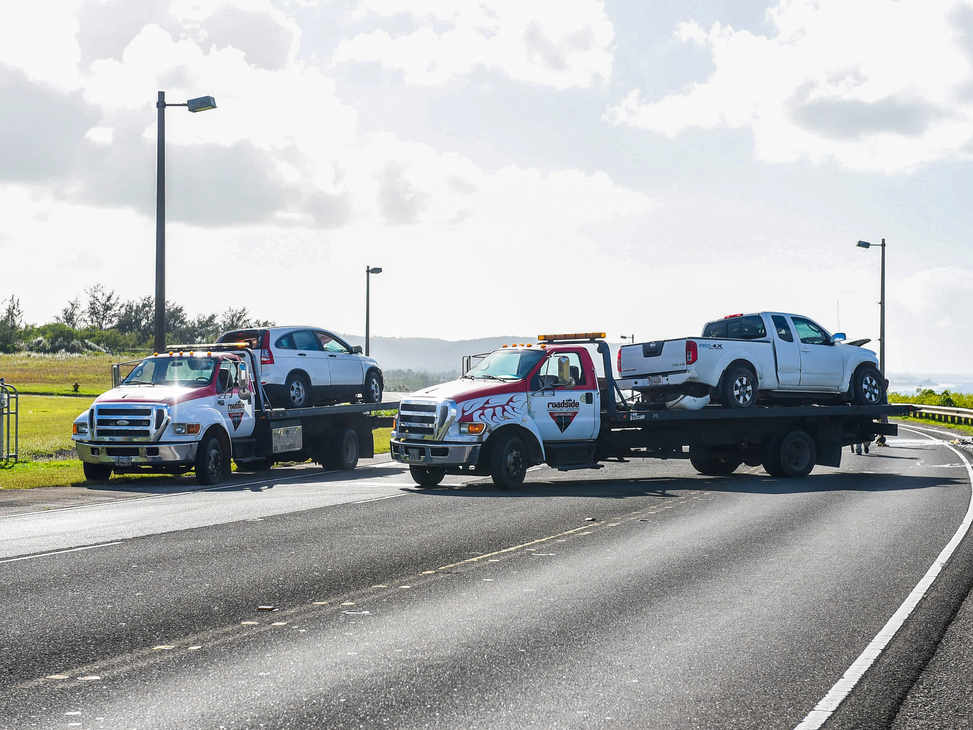 A Honda CR-V sports utility vehicle and a Nissan Frontier pickup can be seen loaded on vehicle transports as Guam Police Department officers conduct an investigation of a collision of the automobiles on Route 10A in Barrigada, Jan. 6, 2019.