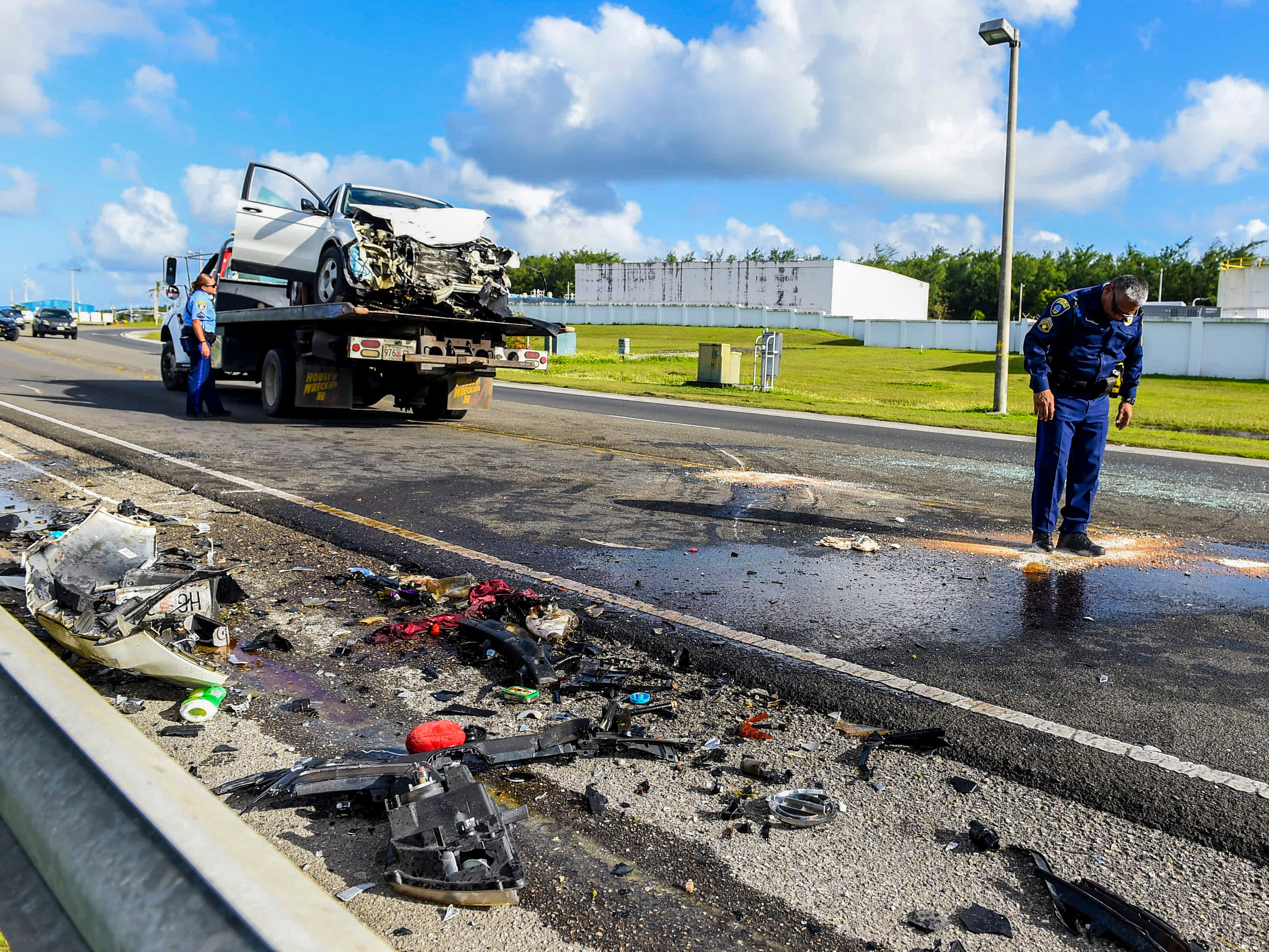 A Nissan Frontier pickup, involved in a two-car collision, can be seen loaded on vehicle transports as Guam Police Department officers conduct an investigation of the crash on Route 10A in Barrigada, Jan. 6, 2019.