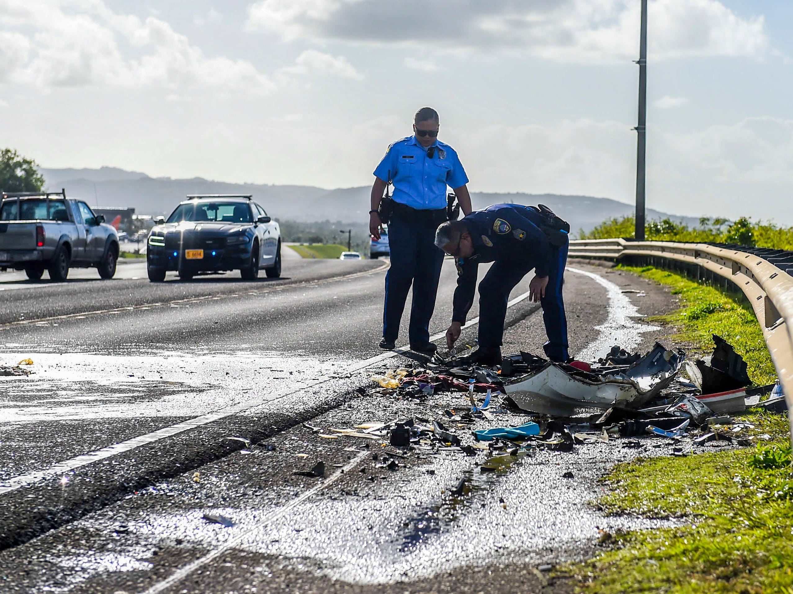 Guam Police Department officers search through crash debris as they conduct an crash investigation involving two vehicles on Route 10A in Barrigada, Jan. 6, 2019.