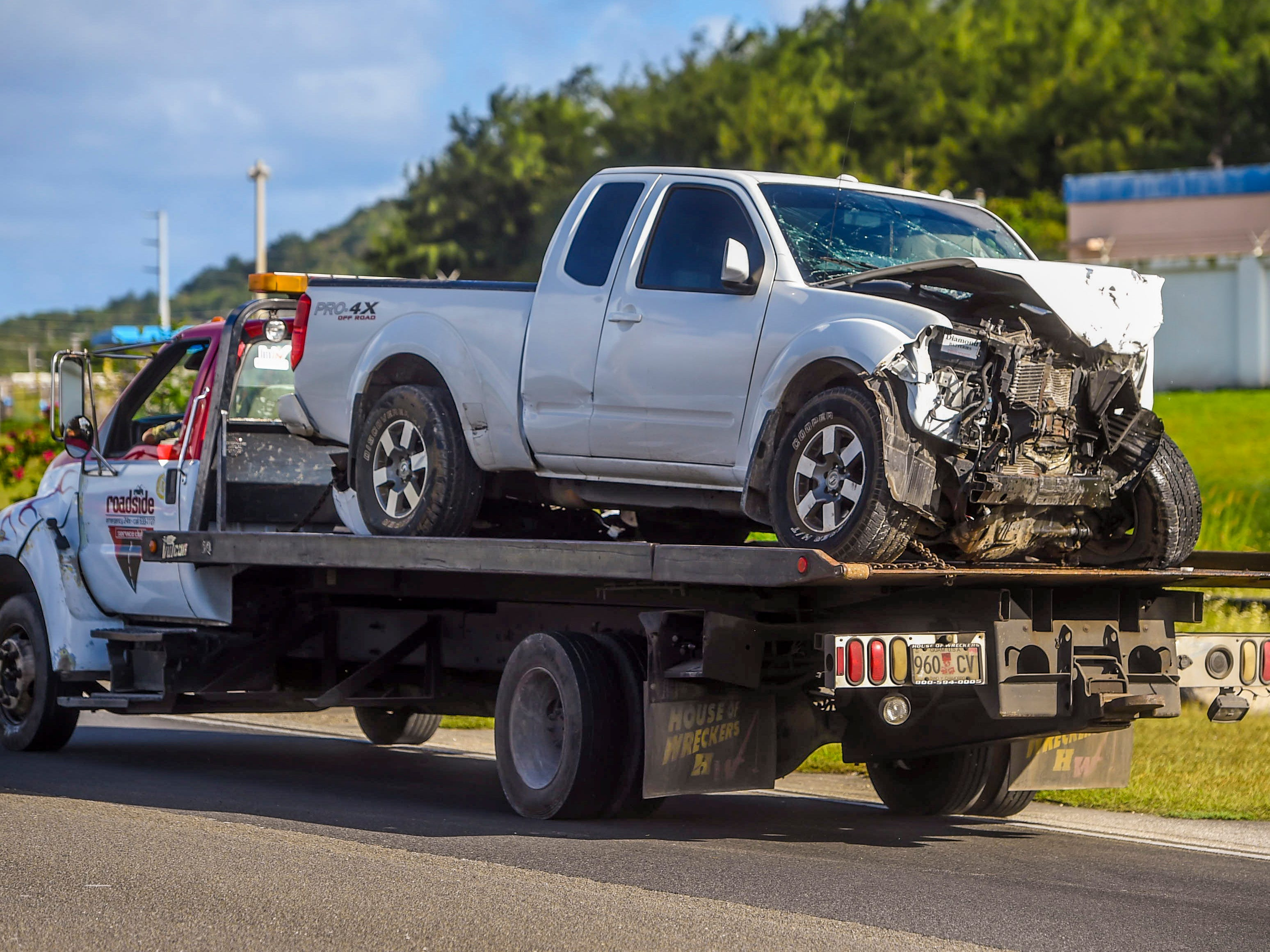 A Nissan Frontier pickup with a smashed front end can be seen loaded on a vehicle transport as Guam Police Department officers conduct an investigation of a crash on Route 10A in Barrigada, Jan. 6, 2019.